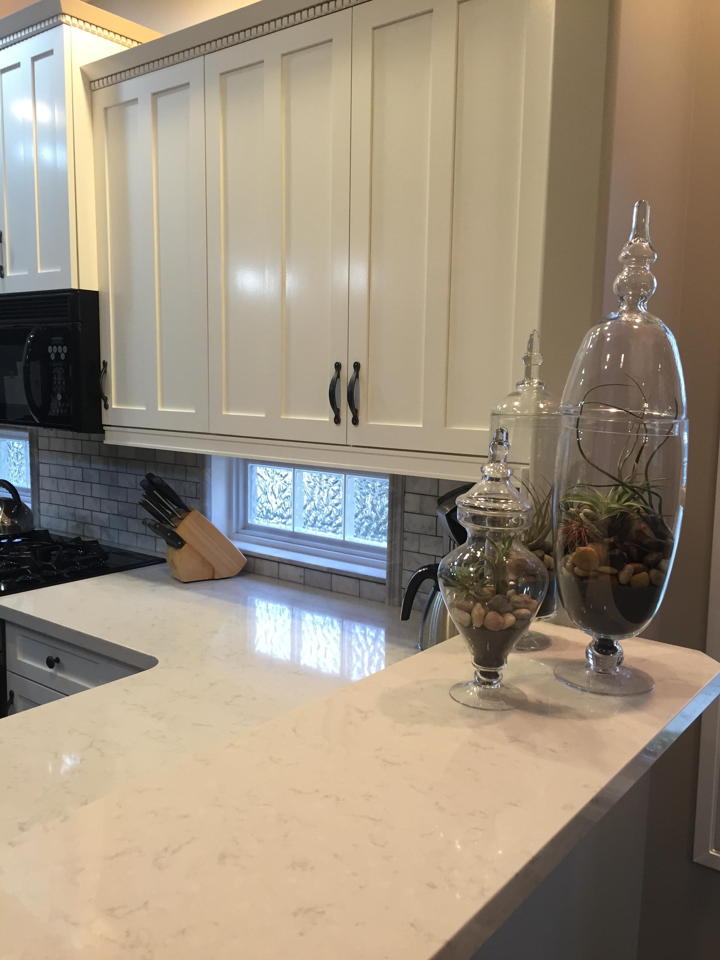 White Quartz countertop, painted cabinetry, marble backsplash.