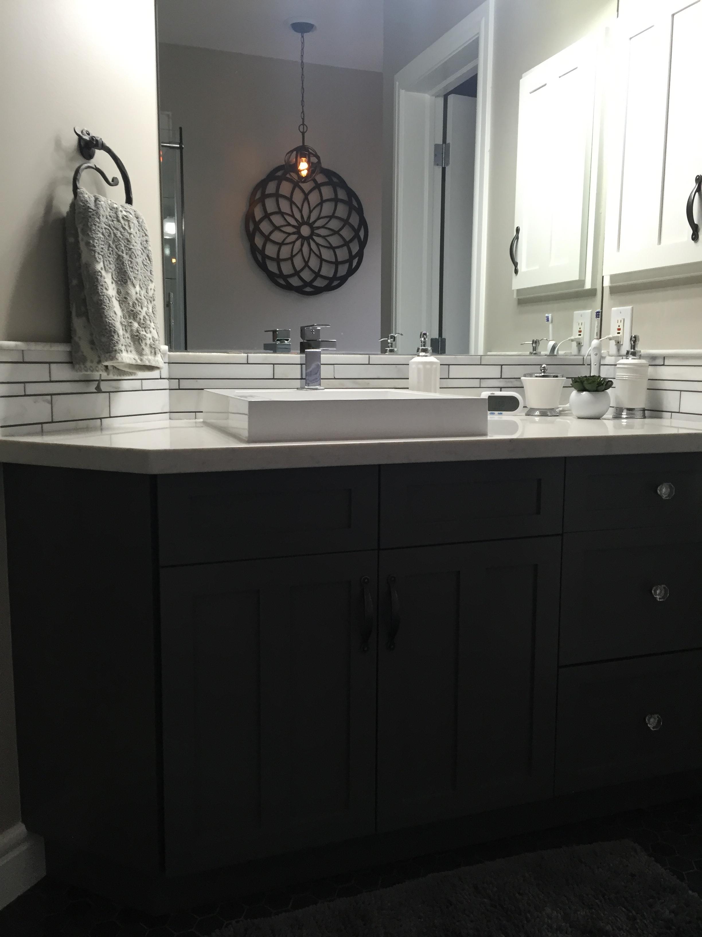 Dark base cabinets, white quartz, marble backsplash.