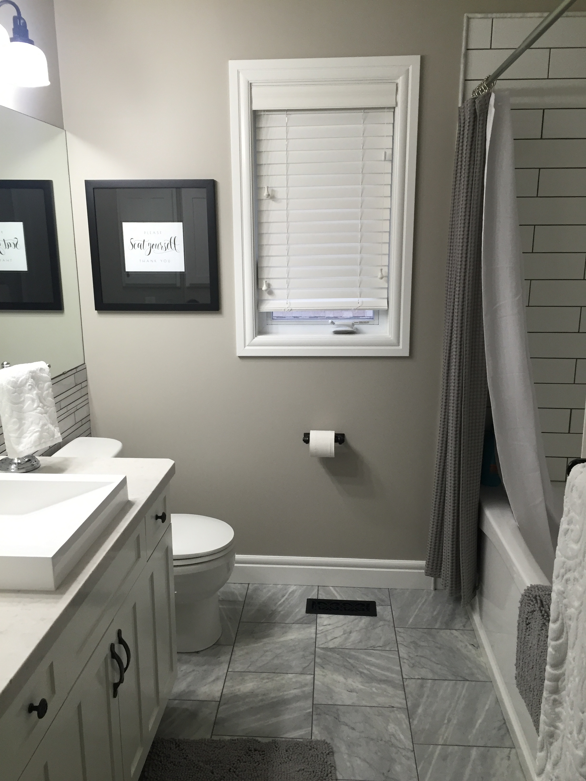 Bianca Carrara floors, white cabinetry, grey walls, white quartz countertops.