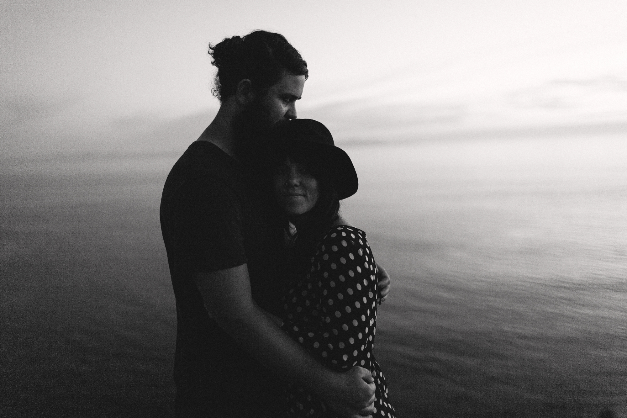 black and white photo of couple at beach