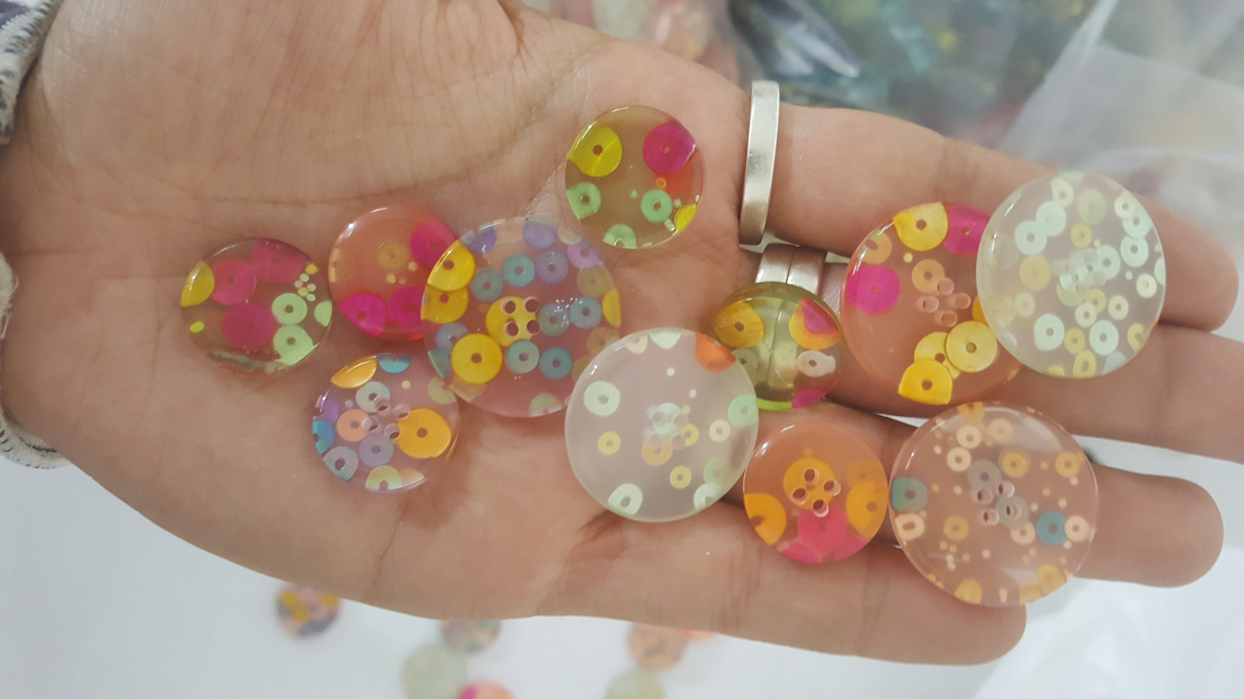 Tailor made sequin-embdedded resin buttons.