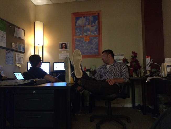 """Tom and Justin (shoes up) in """"The Grotto."""" My desk was where Justin is sitting with the fake bougainvillea."""