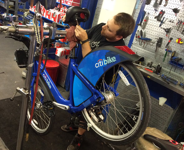 Off with its head: Kevin from City Bikes removes the original seat on Citi Bike.