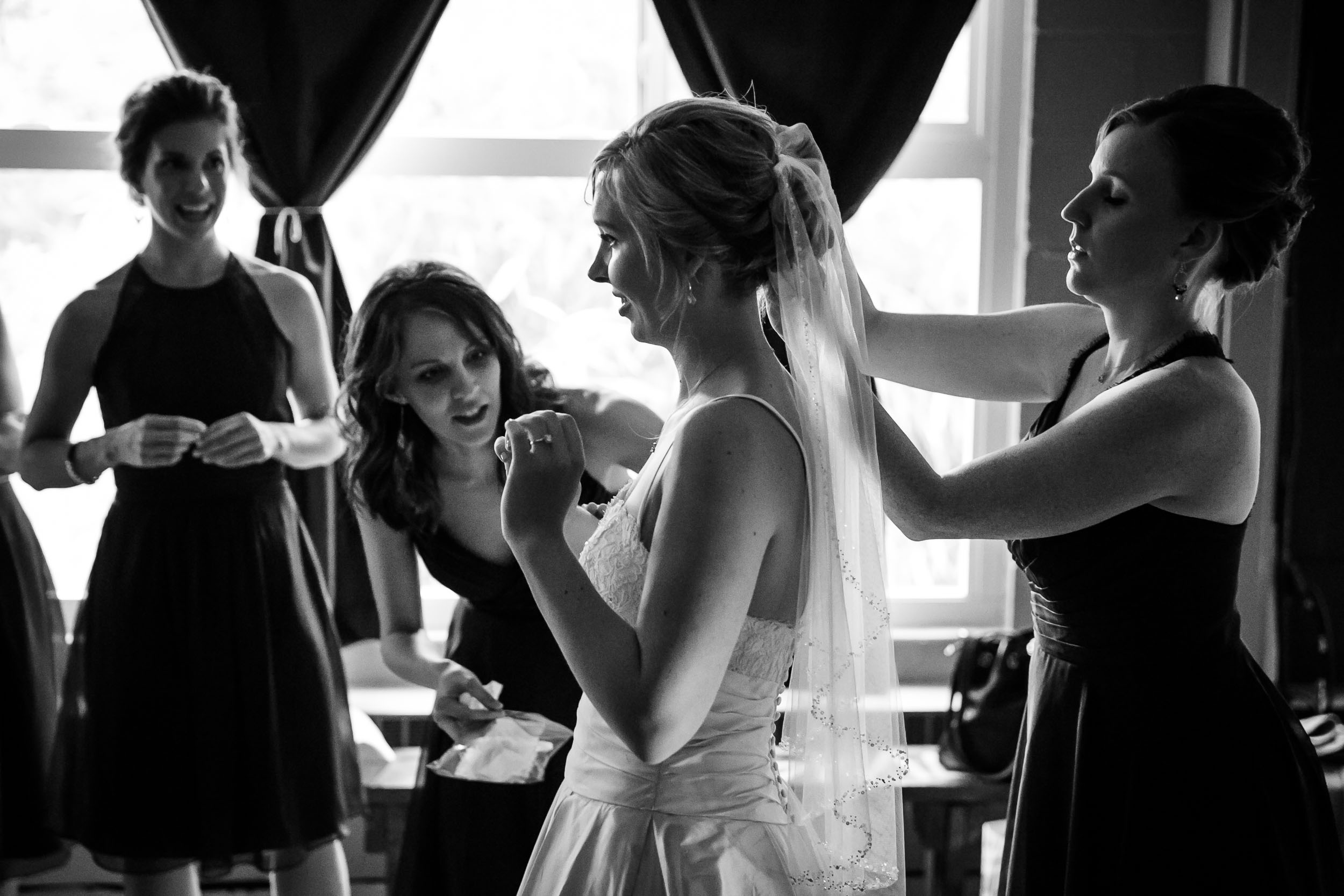 Seattle Community Church Wedding Photography | By G. Lin Photography | Gorgeous shot of bridesmaid pinning veil on bride