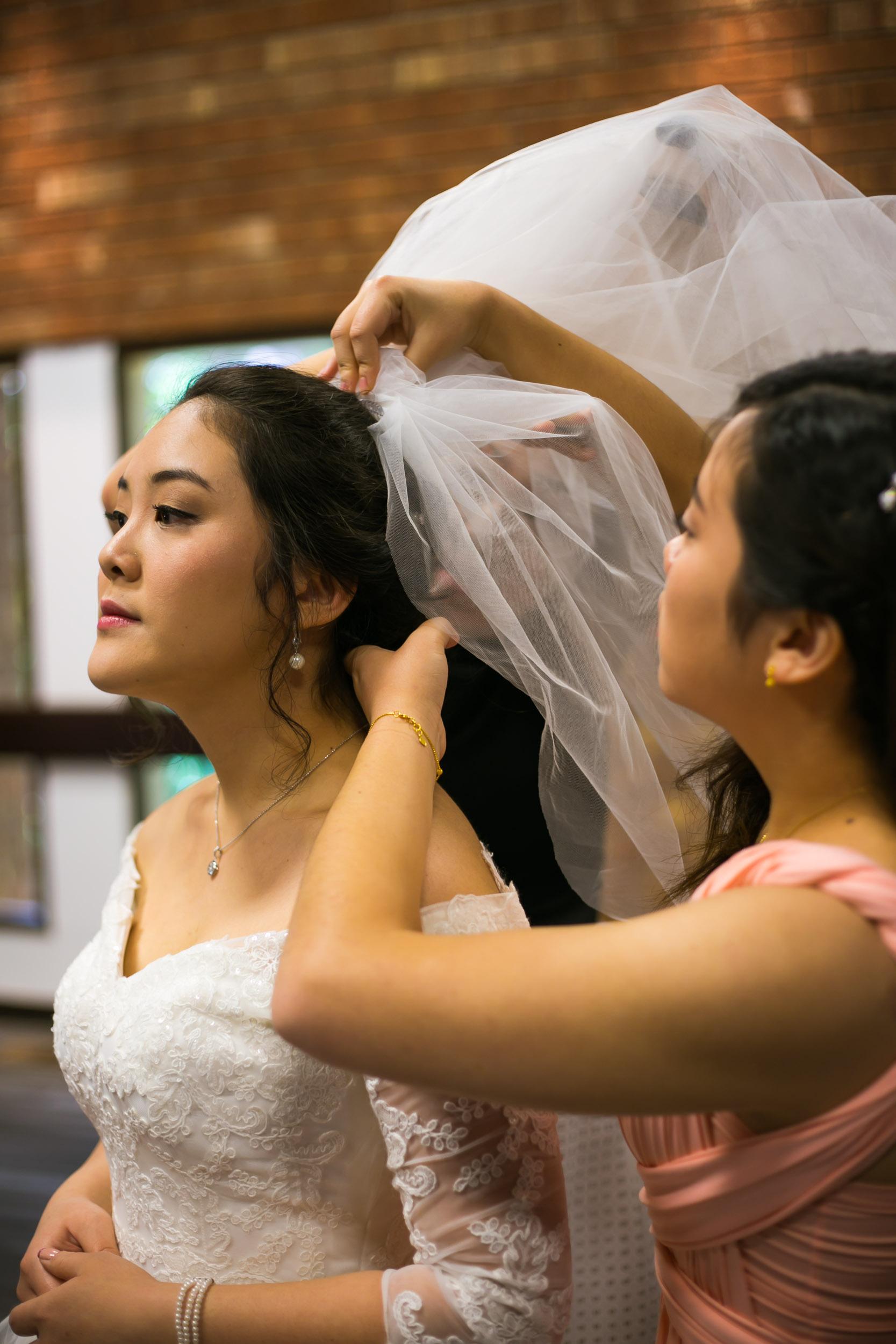 Raleigh Wedding Photographer | G. Lin Photography | Woman helping bride put on veil