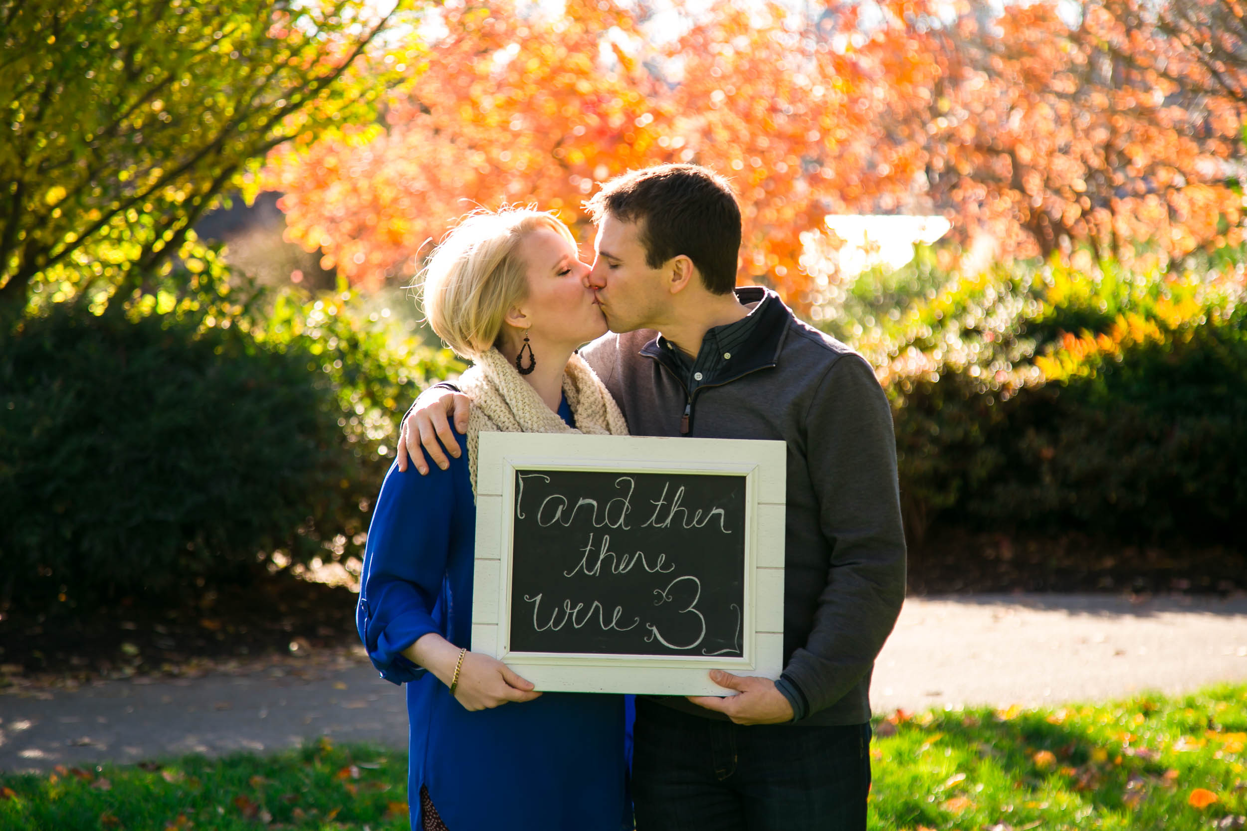 Seattle Family Photographer | G. Lin Photography | Couple holding sign and kissing in Bellevue Park