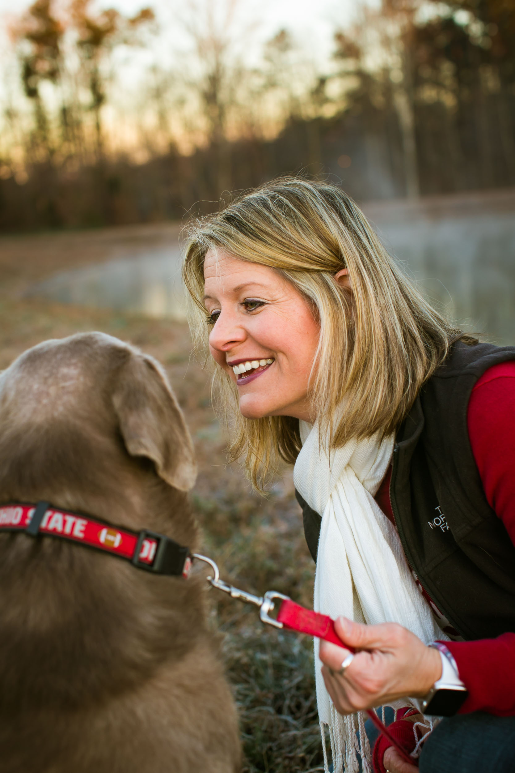 Durham Family Photographer | G. Lin Photography | Woman looking at dog and smiling at park