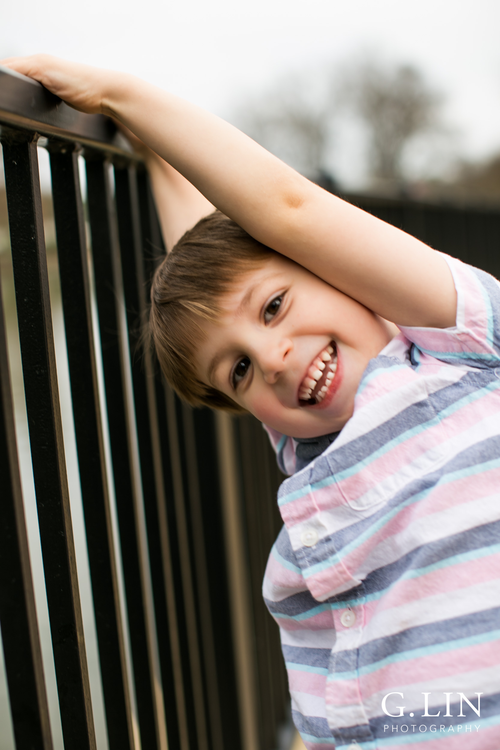 Raleigh Family Photographer | G. Lin Photography | Boy next to fence and smiling