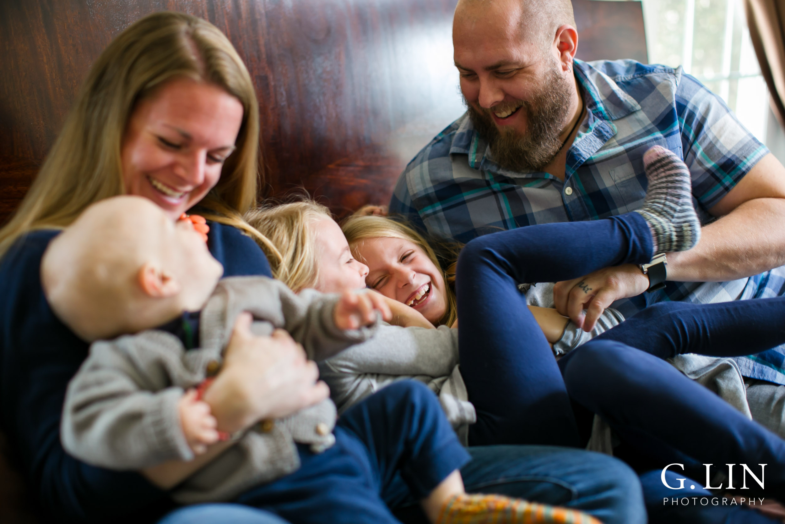 Smiling family on bed for Raleigh family photo