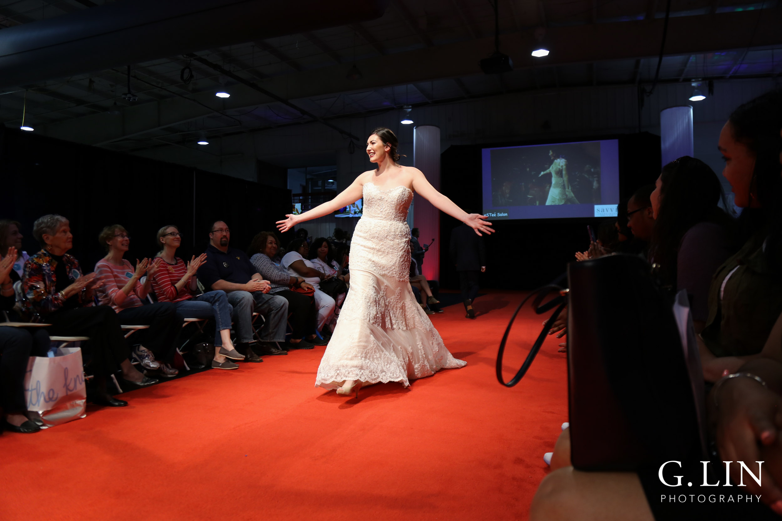 Raleigh Event Photographer | G. Lin Photography | Female model walking down runway wearing strapless bridal gown