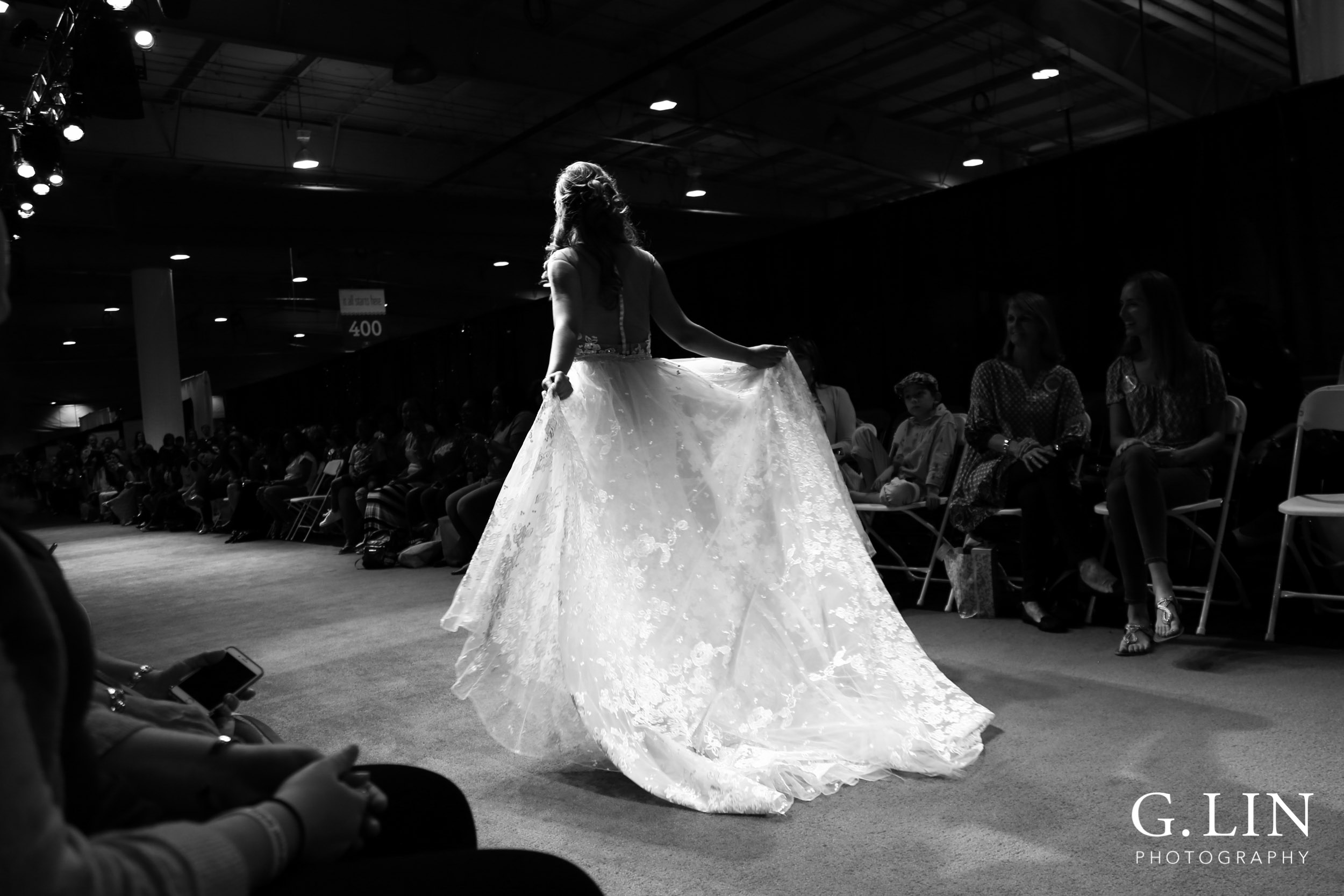 Raleigh Event Photographer | G. Lin Photography | Black and white photo of model walking down runway holding dress