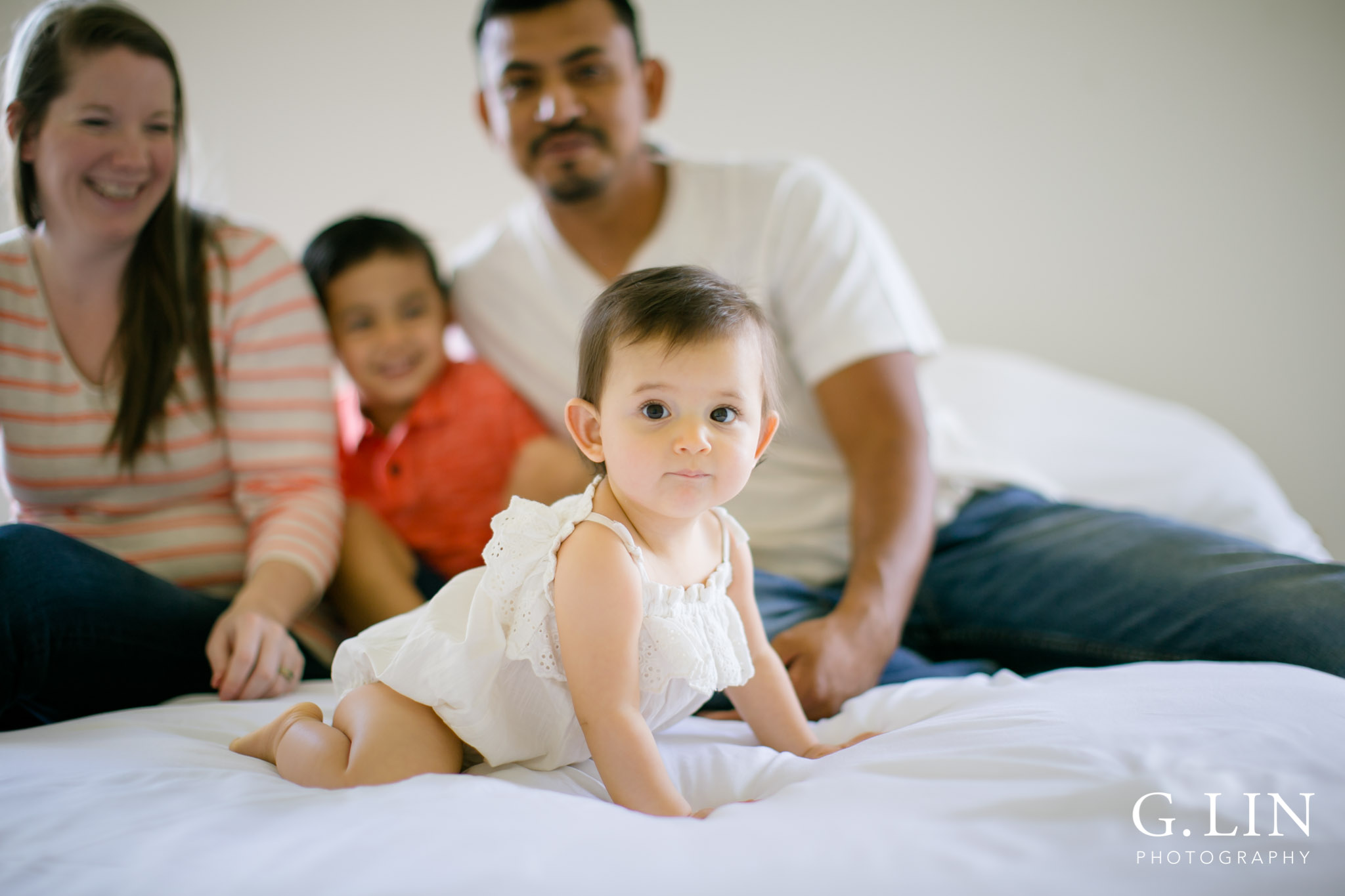 G. Lin Photography | Durham Family Photographer | Baby girl sitting on white bed with family in the background
