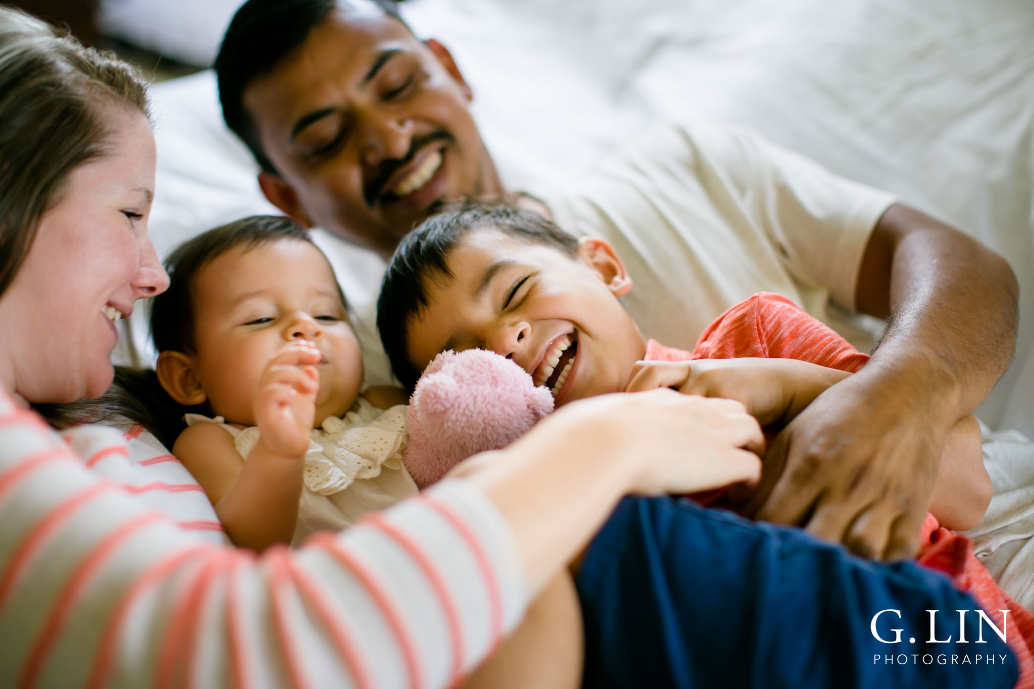 G. Lin Photography | Durham Family Photographer | Family on white bed tickling each other
