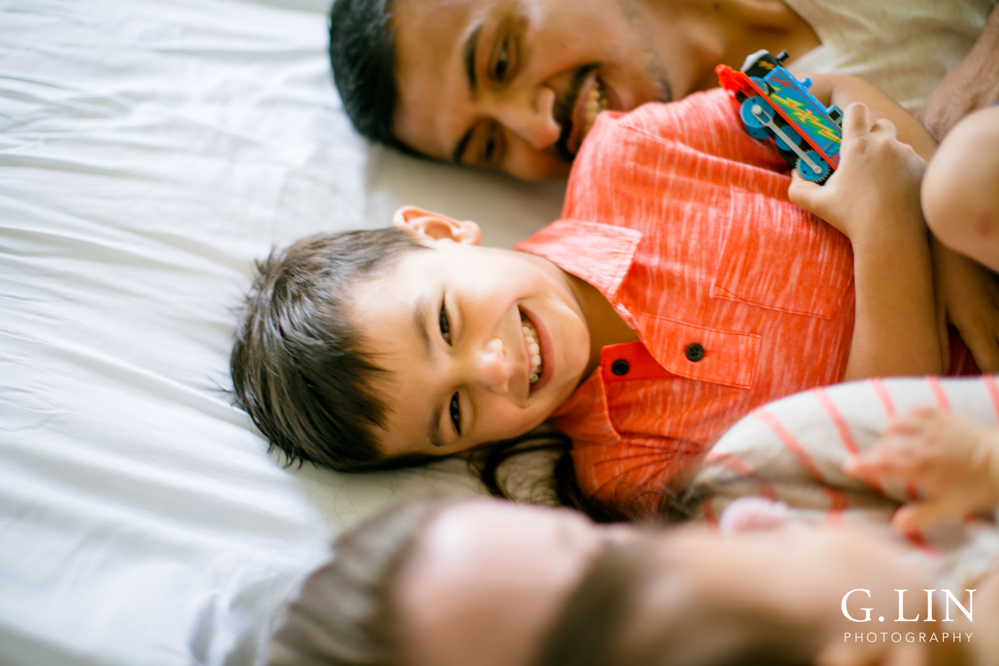 G. Lin Photography | Durham Family Photographer | Boy sitting on white bed smiling at camera