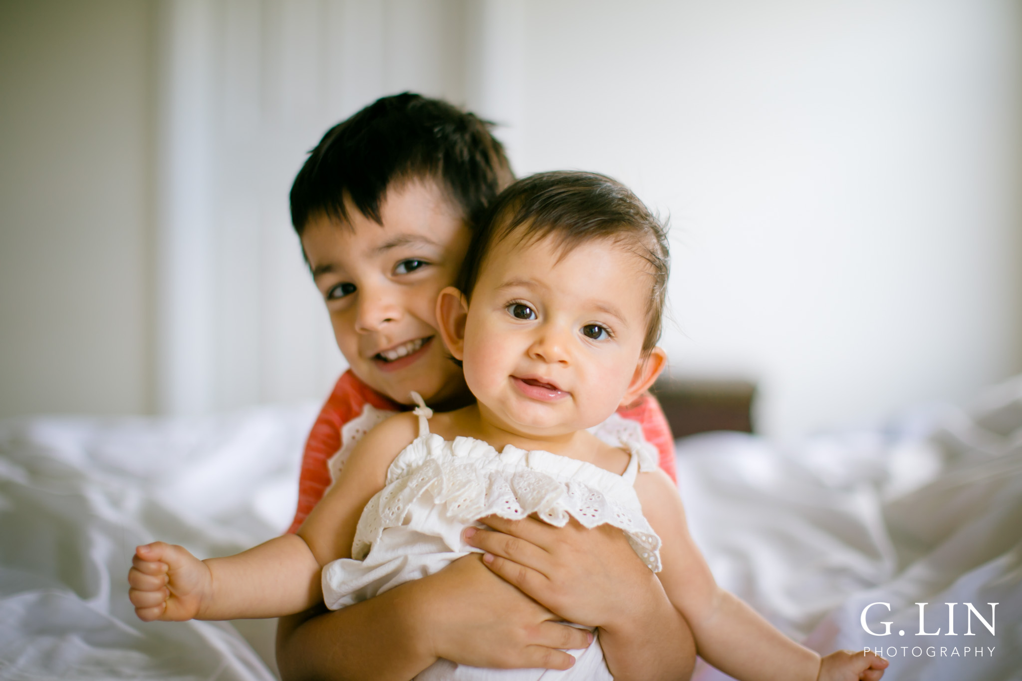 G. Lin Photography   Durham Family Photographer   Boy holding baby sister on white bed