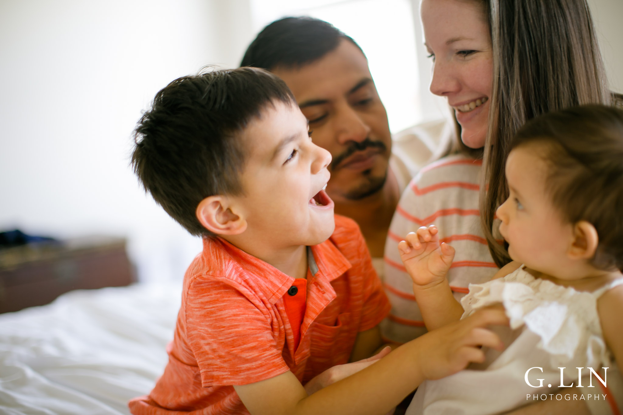 G. Lin Photography   Durham Family Photographer   Boy tickling little sister with family on bed