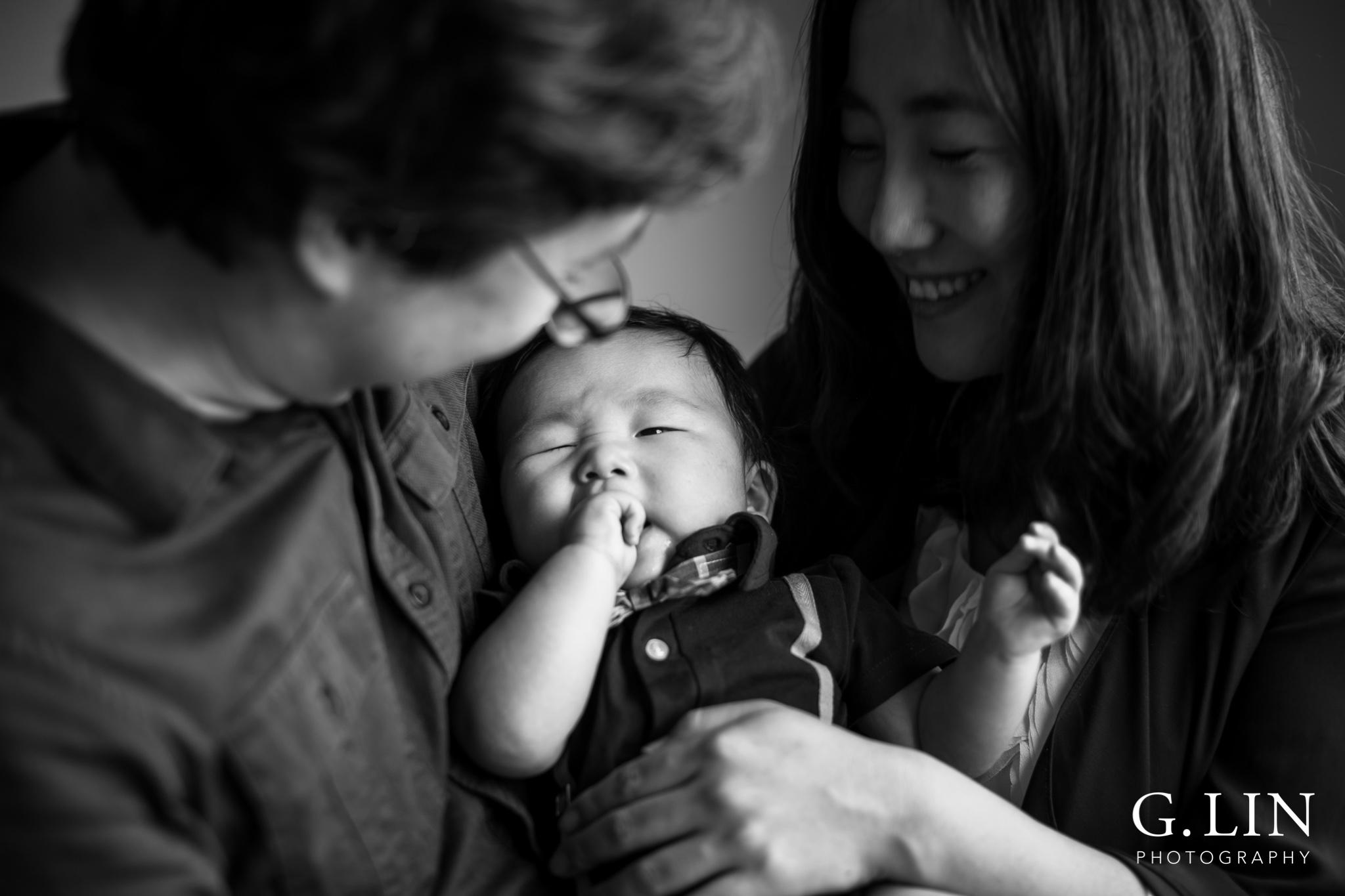 Raleigh Family Photographer | G. Lin Photography | Baby yawning in parents arms, photo in black and white