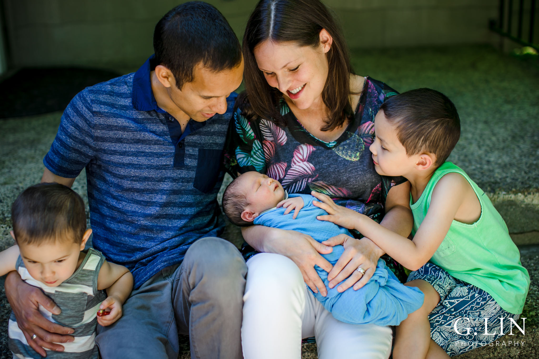 Raleigh Family Photographer | G. Lin Photography | Family outside of home and looking at baby