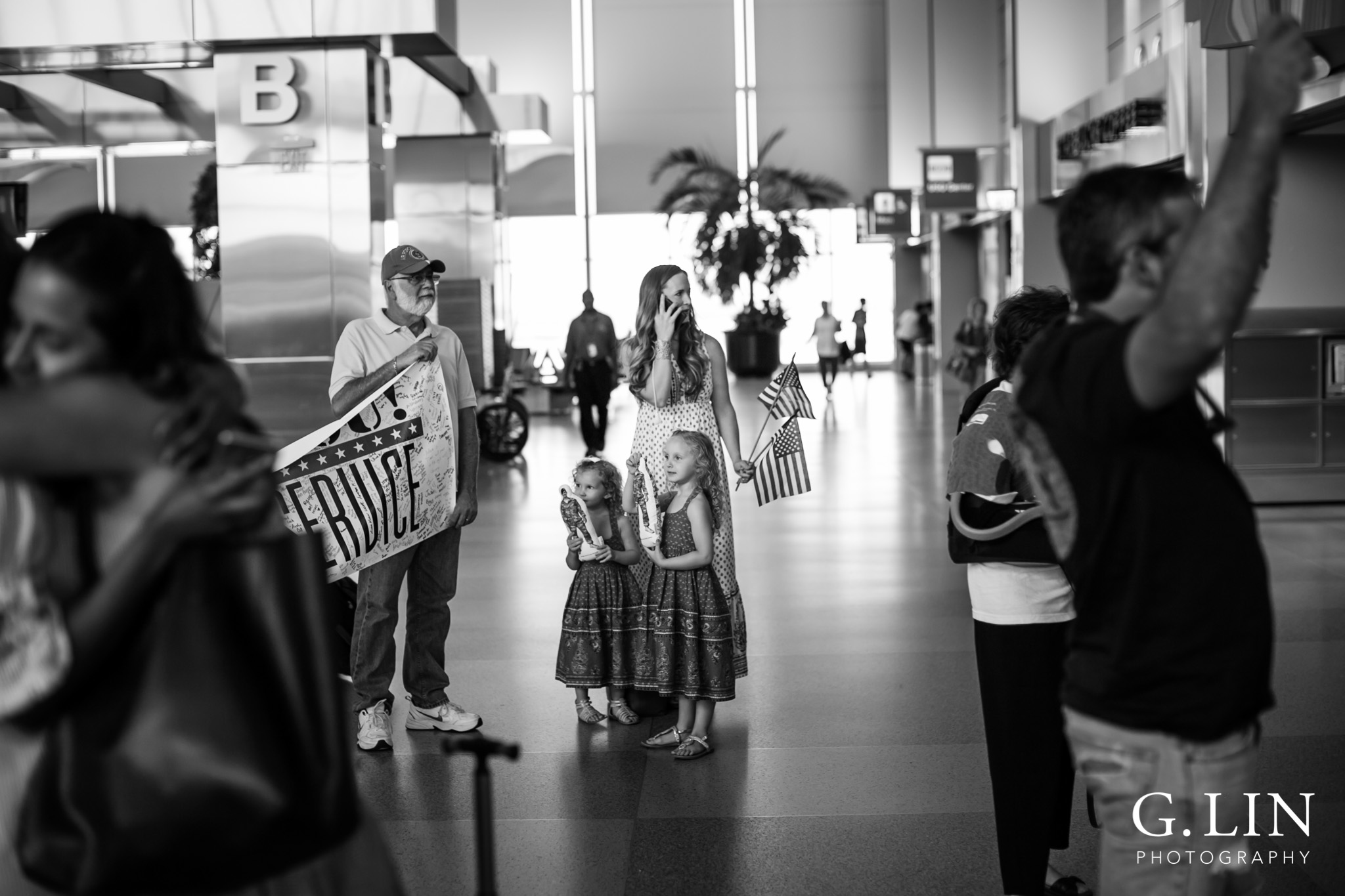 Raleigh Family Photographer | G. Lin Photography | wife on the phone waiting for husband at airport