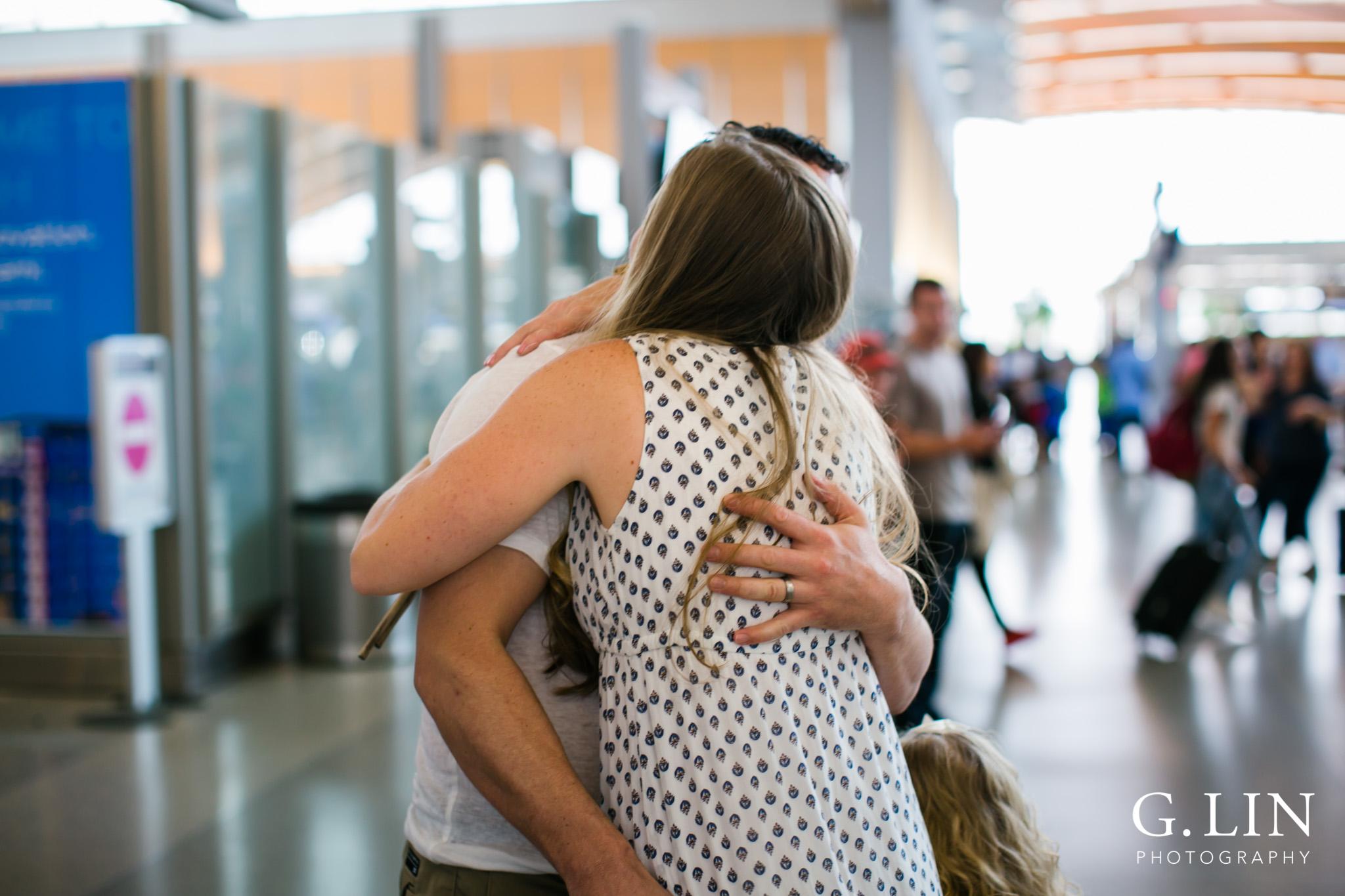Raleigh Family Photographer | G. Lin Photography | dad hugging and greeting his wife at airport