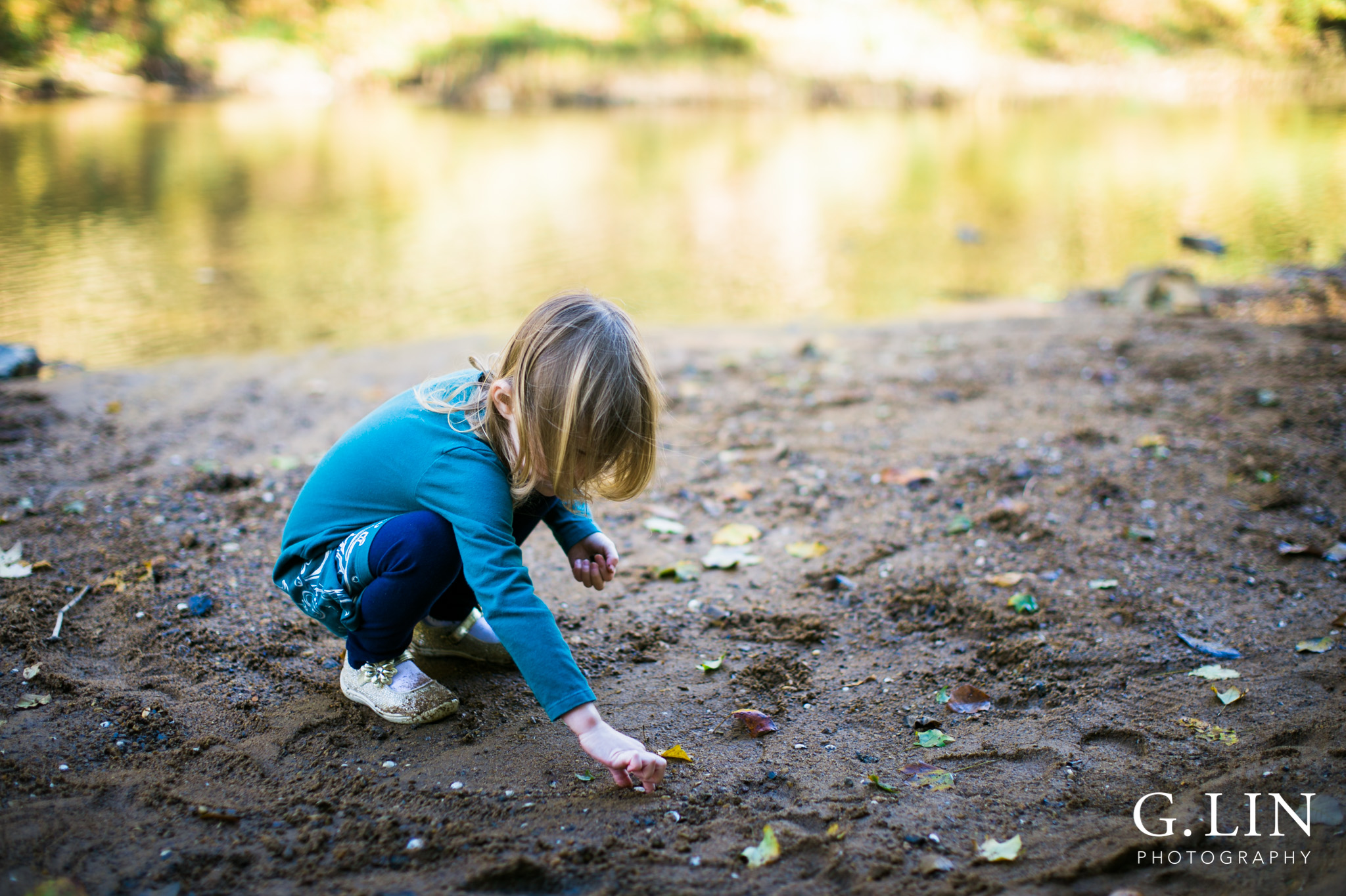 Durham Family Photographer | G. Lin Photography | Close up of child playing by the river and holding sand