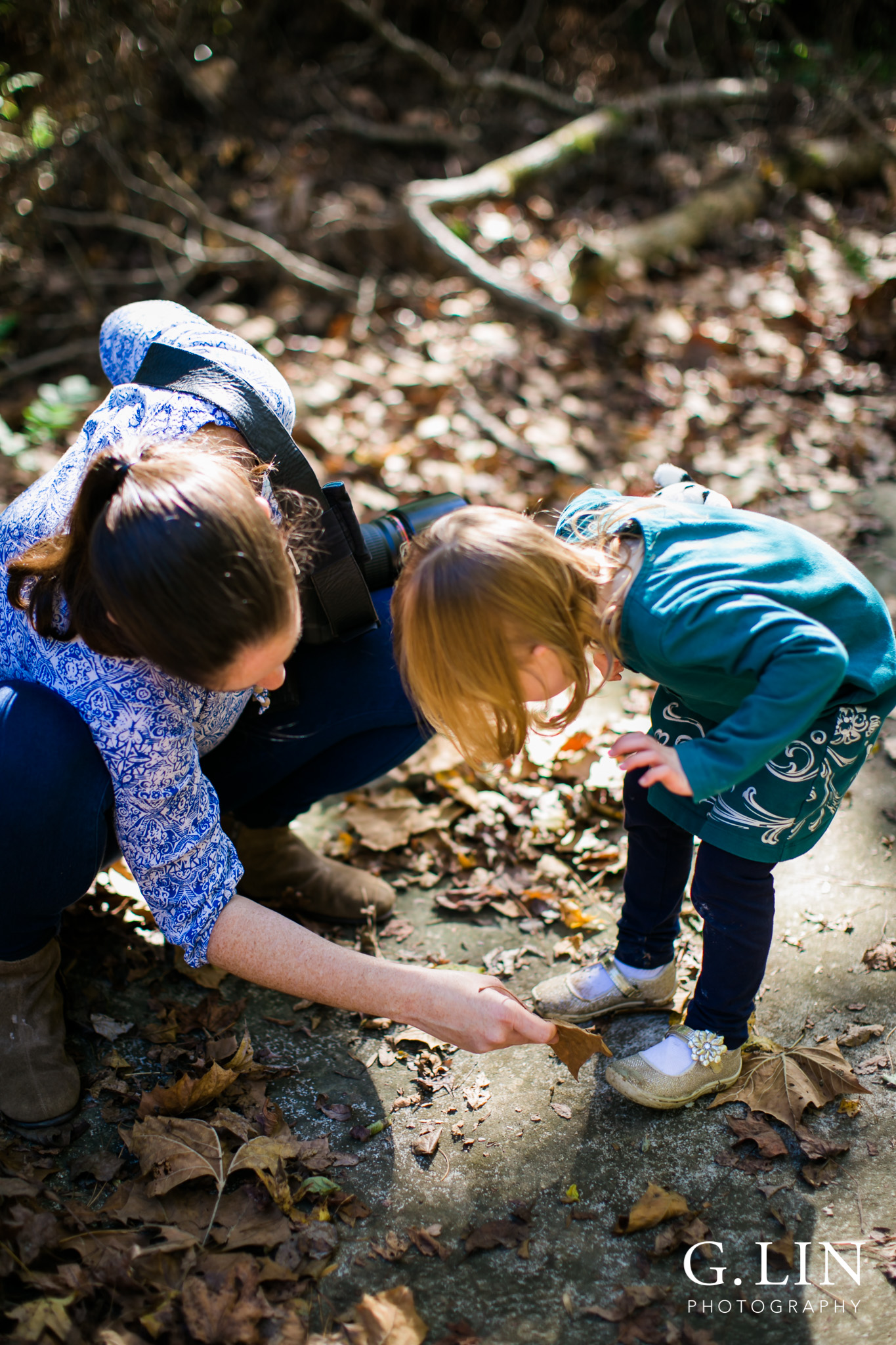 Durham Family Photographer | G. Lin Photography | Mother wiping off dirt from daughter's shoes