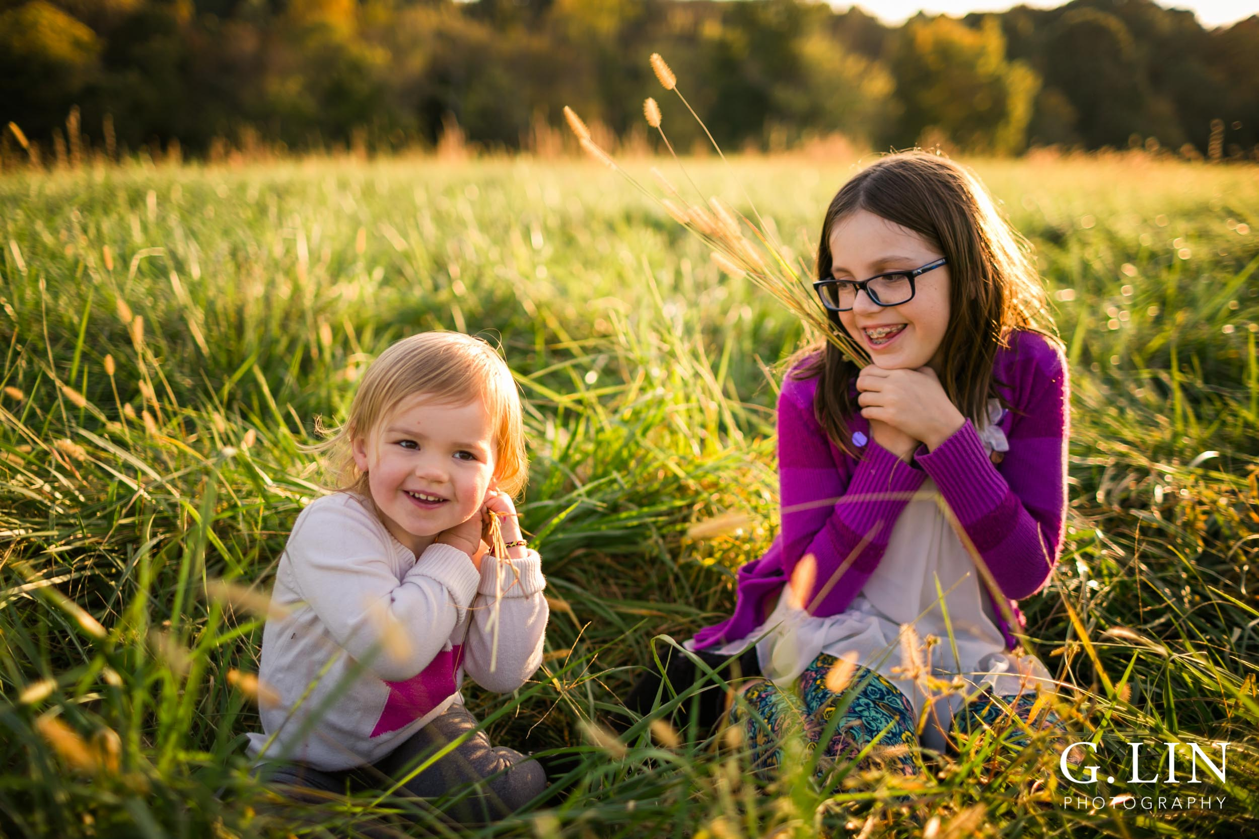 Sisters sitting in an open field | Raleigh Family Photographer | G. Lin Photography