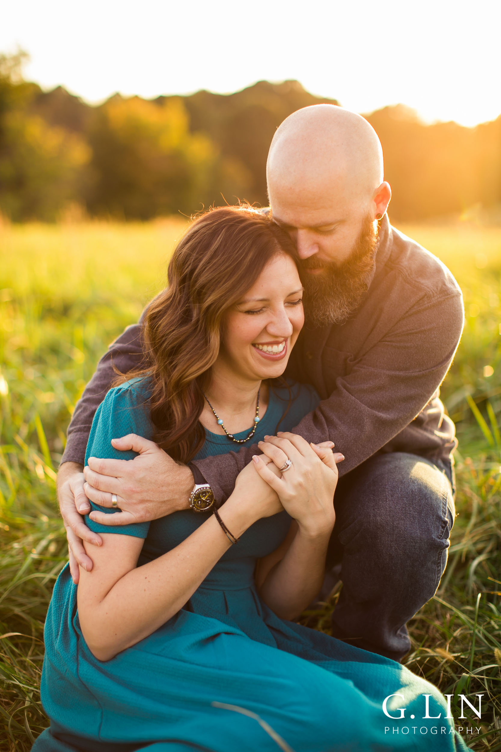 Couple laughing with each other sitting in open field during sunset | Raleigh Family Photographer | G. Lin Photography