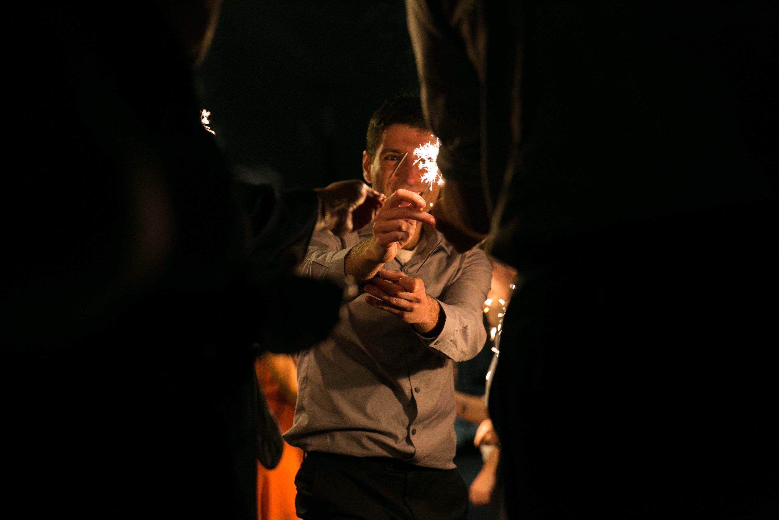 Man lighting sparkler for wedding sendoff   Durham Wedding Photographer   By G. Lin Photography