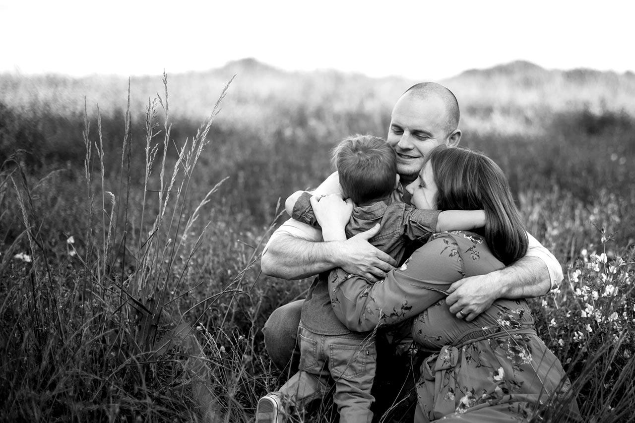 Durham Family Photographer | G. Lin Photography | Family of three hugging in the fields