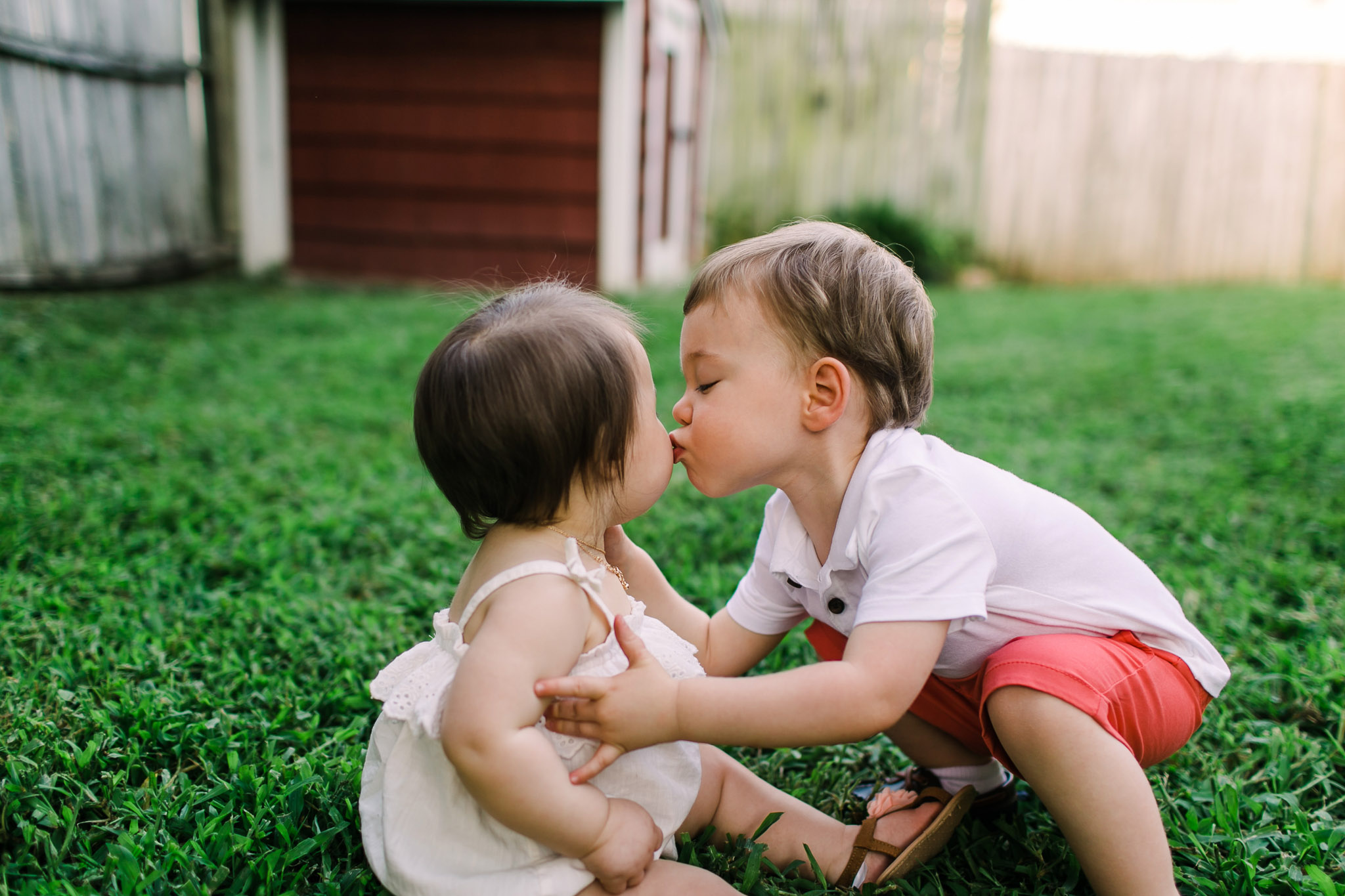 Brother kissing little sister on cheek | Raleigh Children Photography | By G. Lin Photography