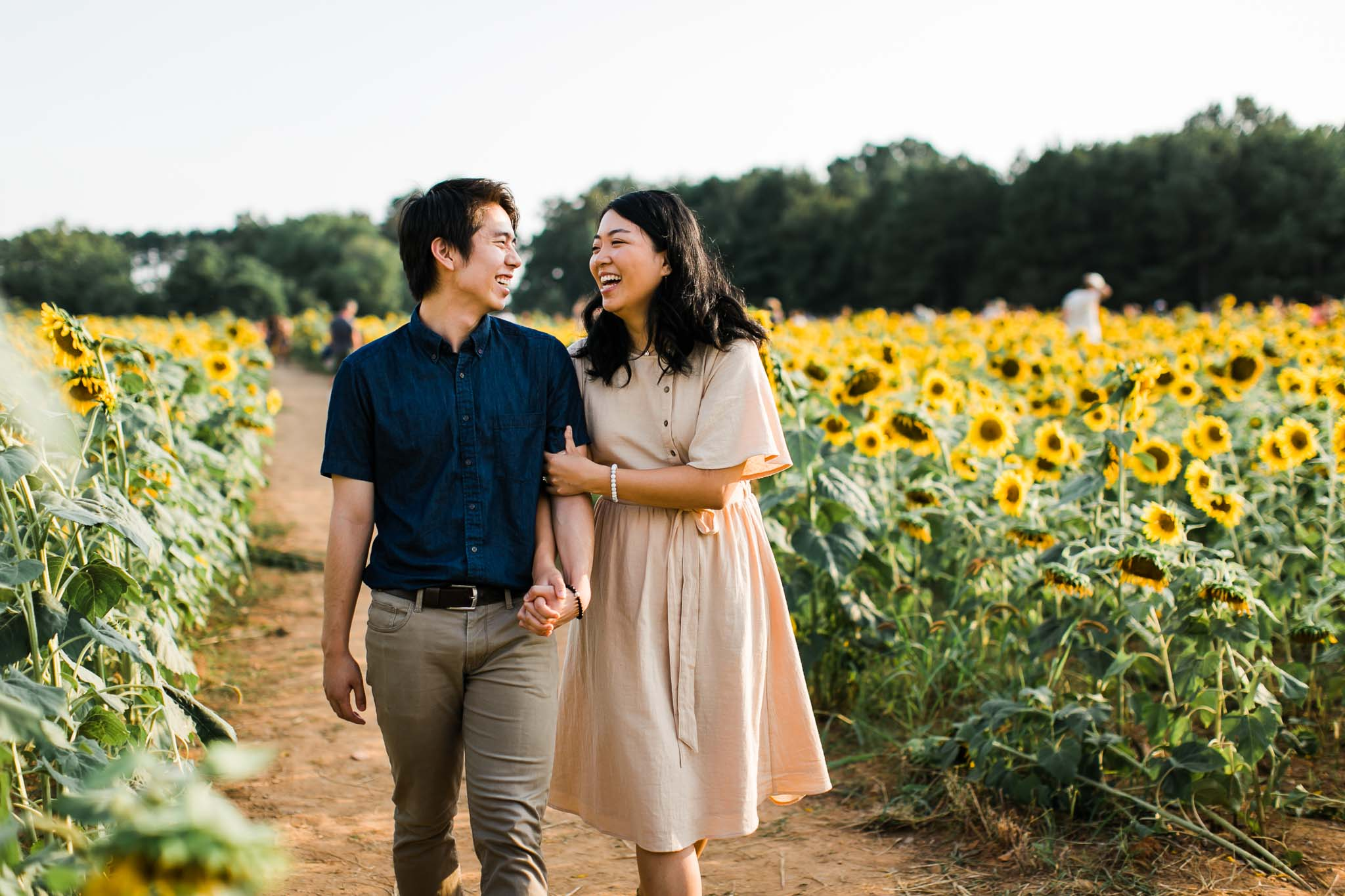 Raleigh Engagement Photographer | By G. Lin Photography | Couple walking through sunflower field | Dorothea Dix Park