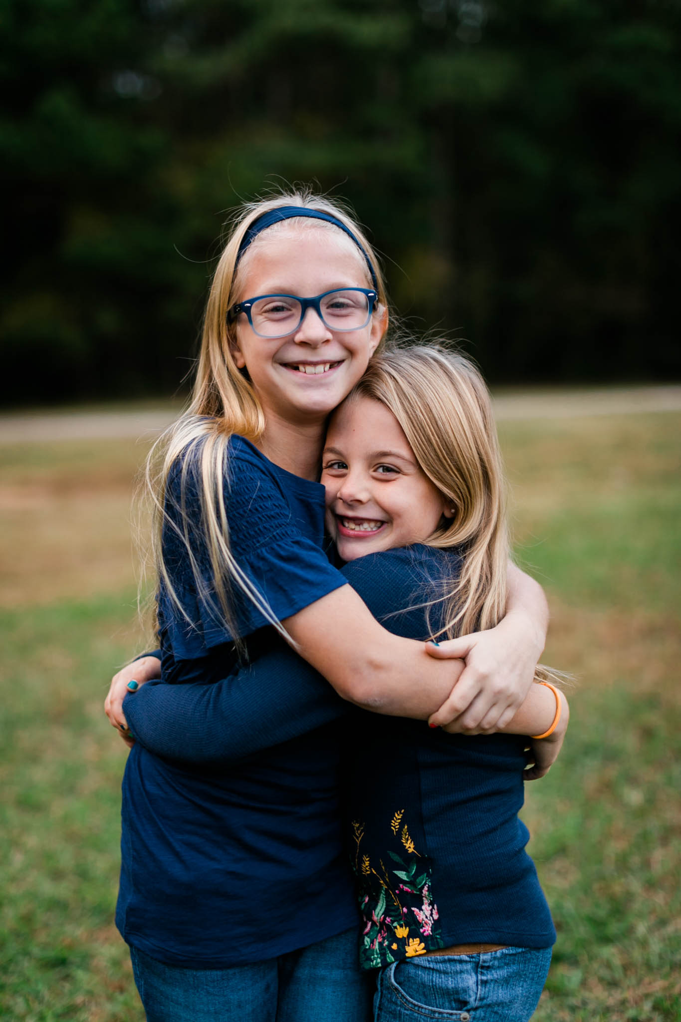 Sisters hugging each other at Umstead Park | Raleigh Family Photographer | By G. Lin Photography