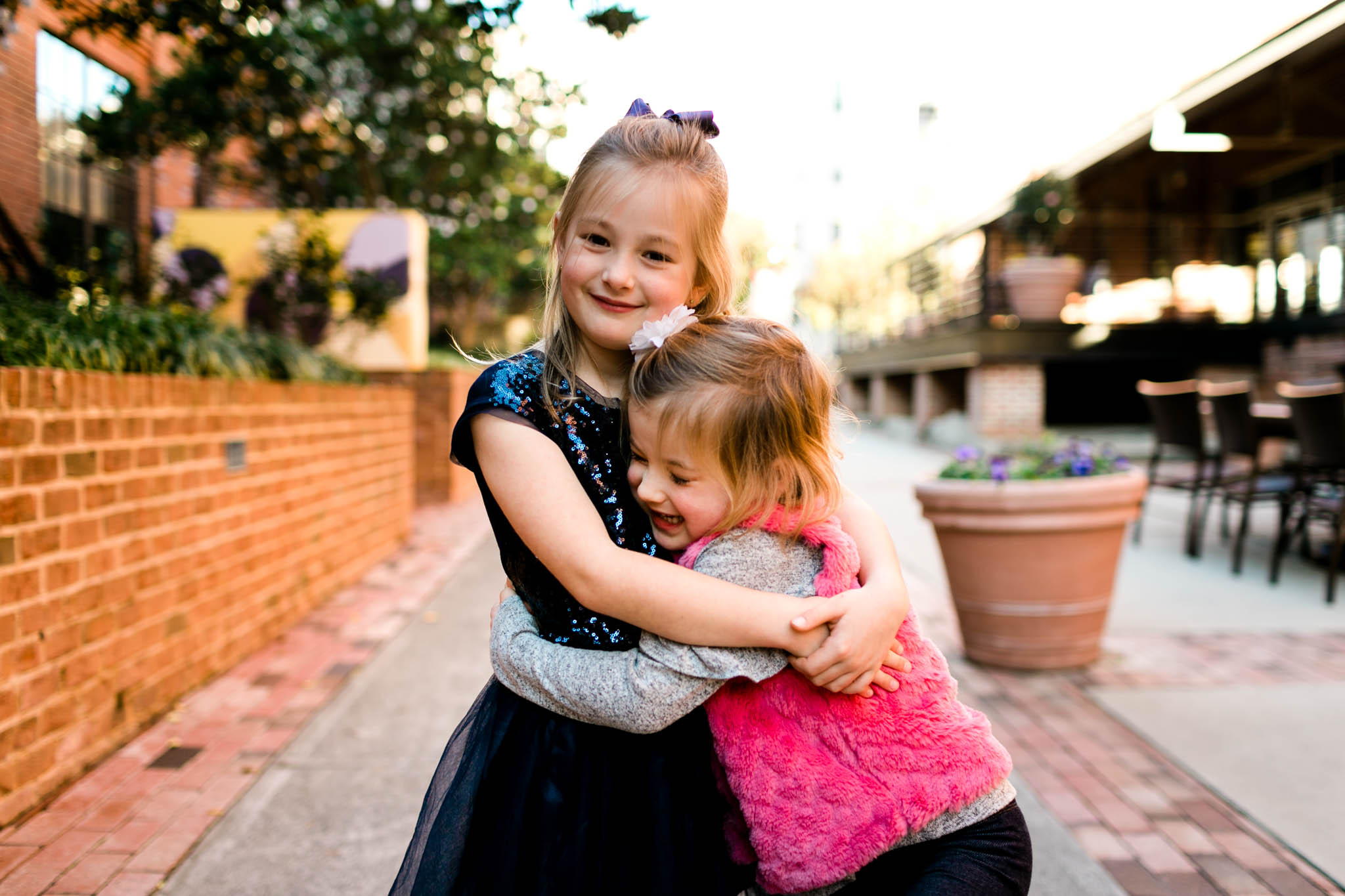 Sisters hugging each other | Durham Family Photographer | American Tobacco Campus | By G. Lin Photography