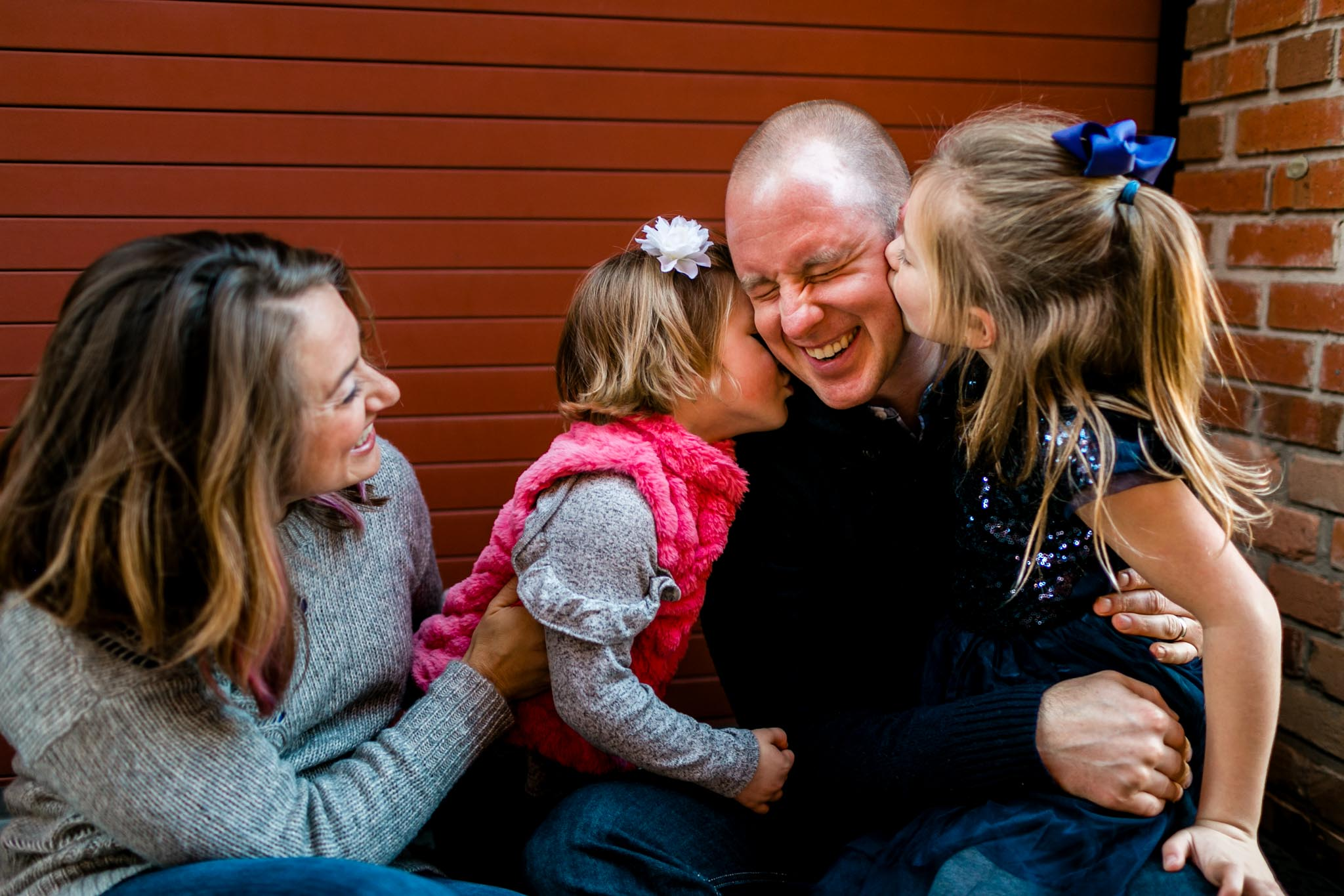 Daughters kissing dad on the cheek | American Tobacco Campus | Durham Family Photography | By G. Lin Photography