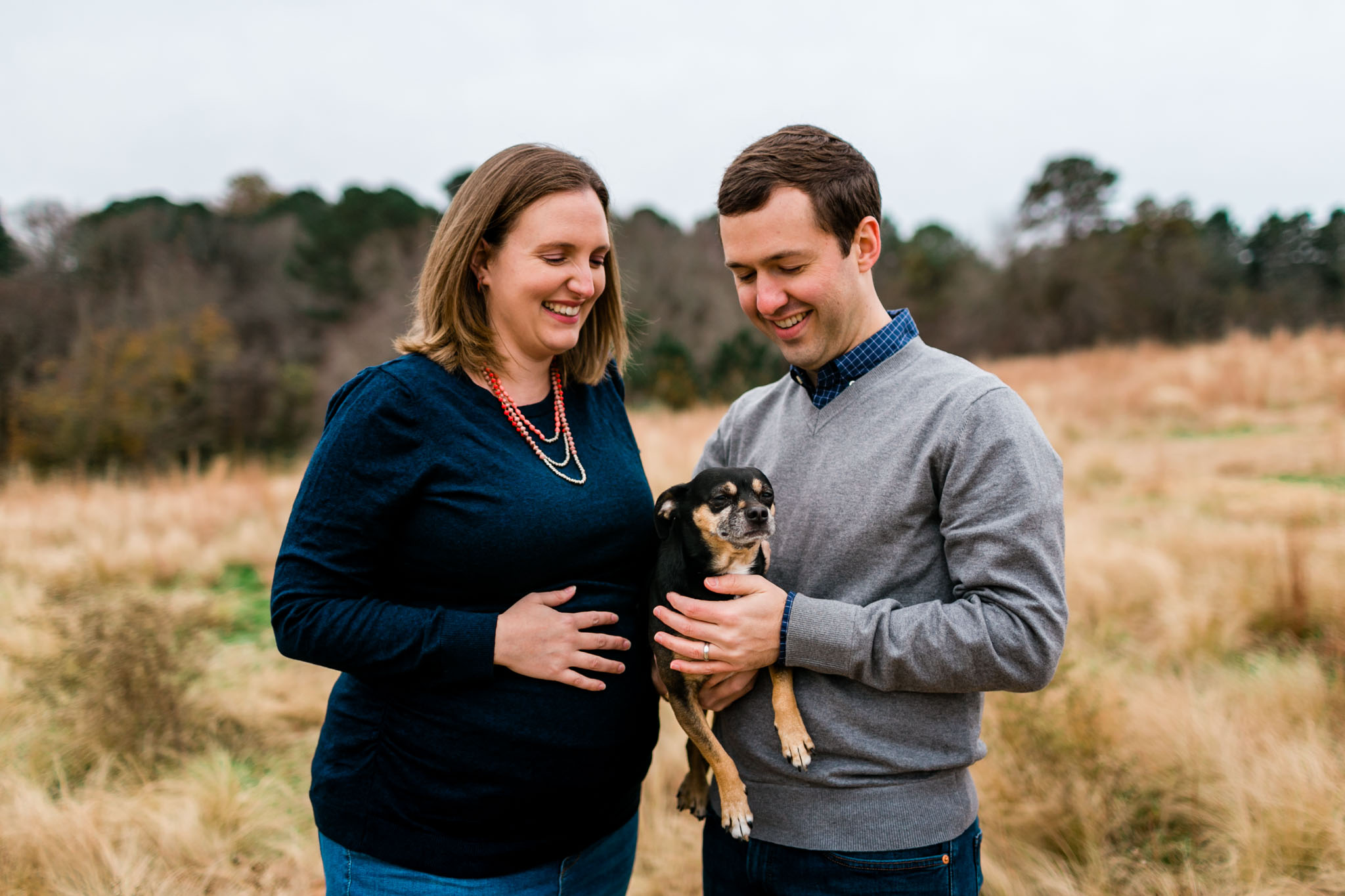 Candid maternity portrait of family with dog in open field | Raleigh Maternity Photographer | By G. Lin Photography