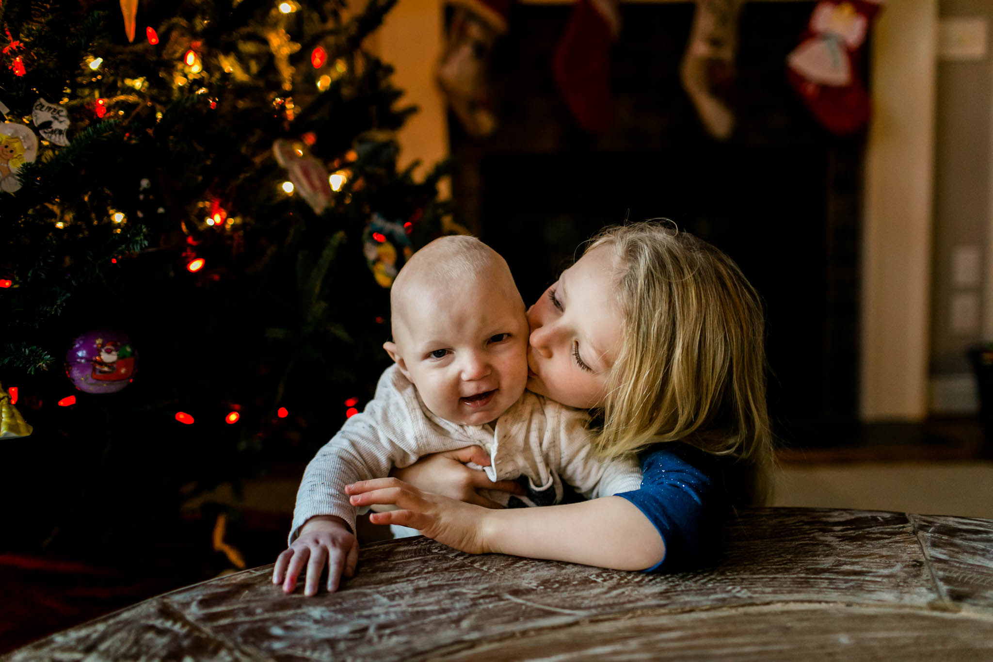 Sister kissing little brother on cheek | By G. Lin Photography | Durham Family Photographer