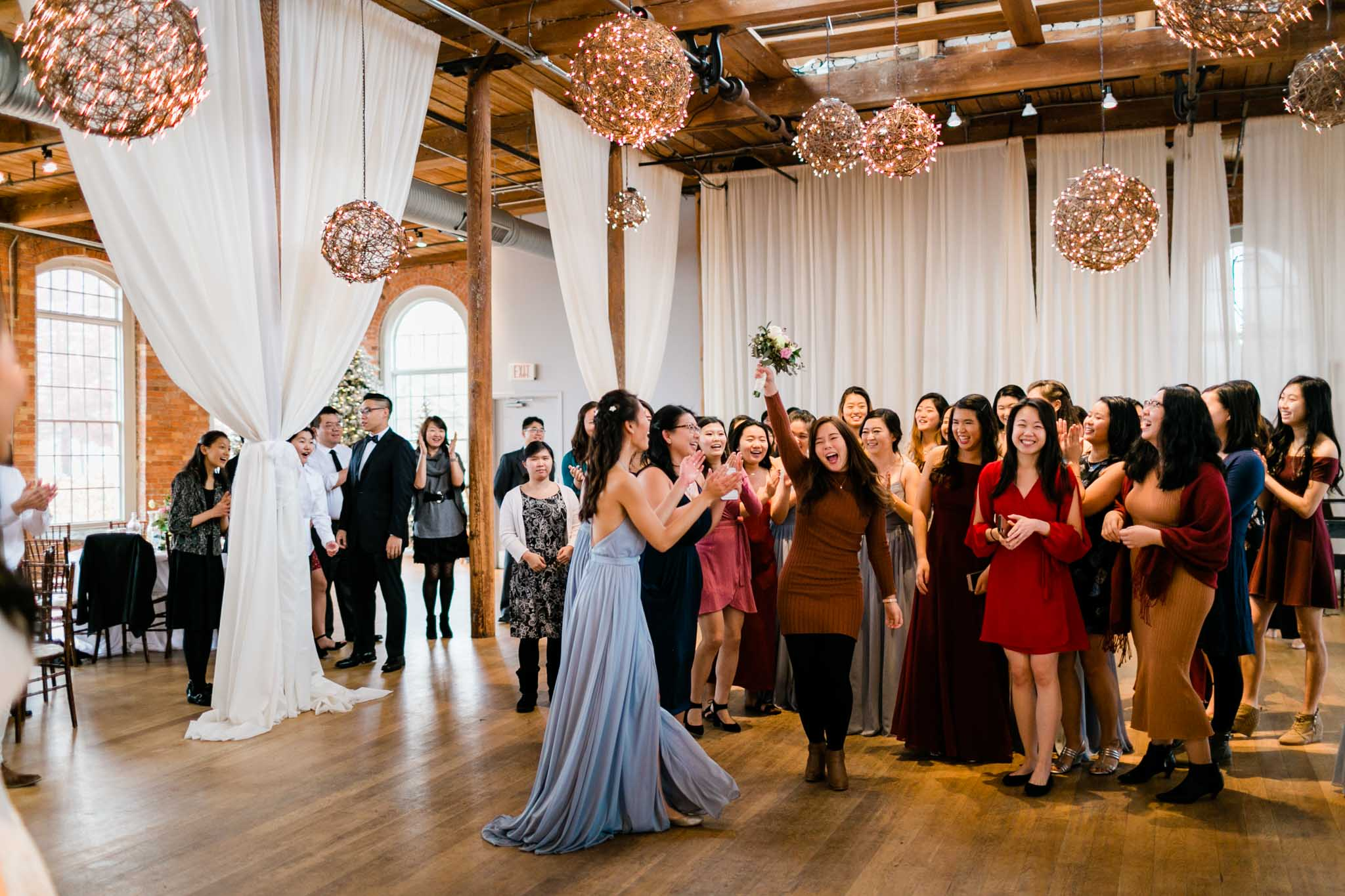 Girl catching bouquet during wedding reception | Durham Wedding Photographer | The Cotton Room, NC | By G. Lin Photography