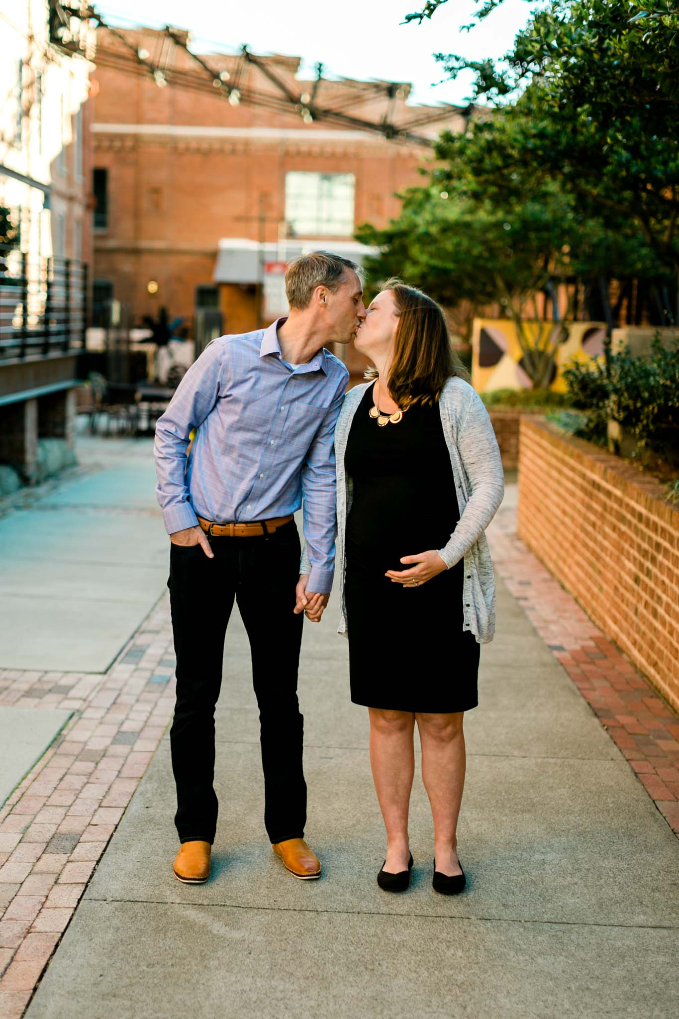 Couple kissing at American Tobacco Campus | Durham Maternity Photography | By G. Lin Photography