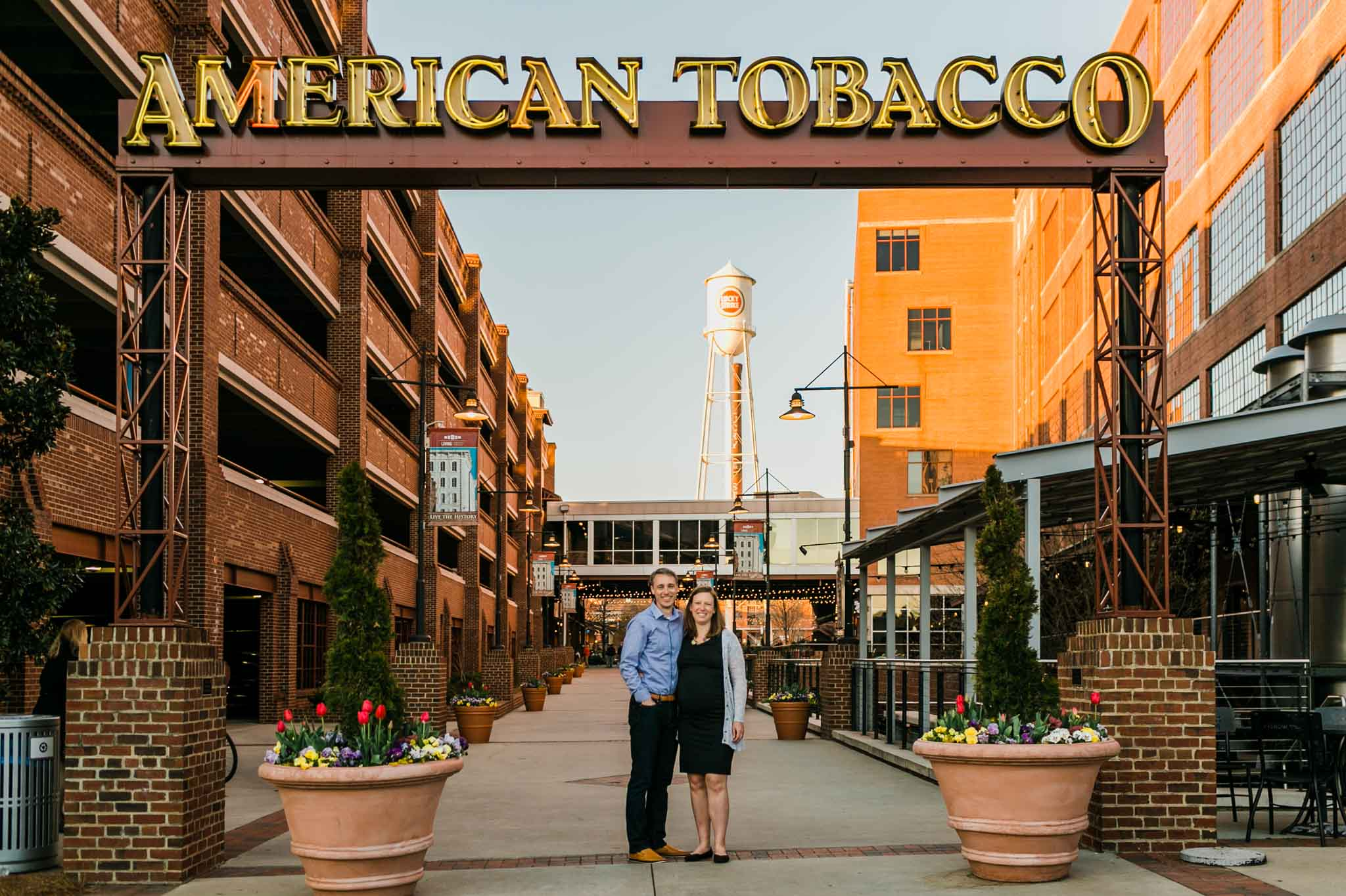 Couple standing by American Tobacco Sign | Durham Family Photographer | By G. Lin Photography