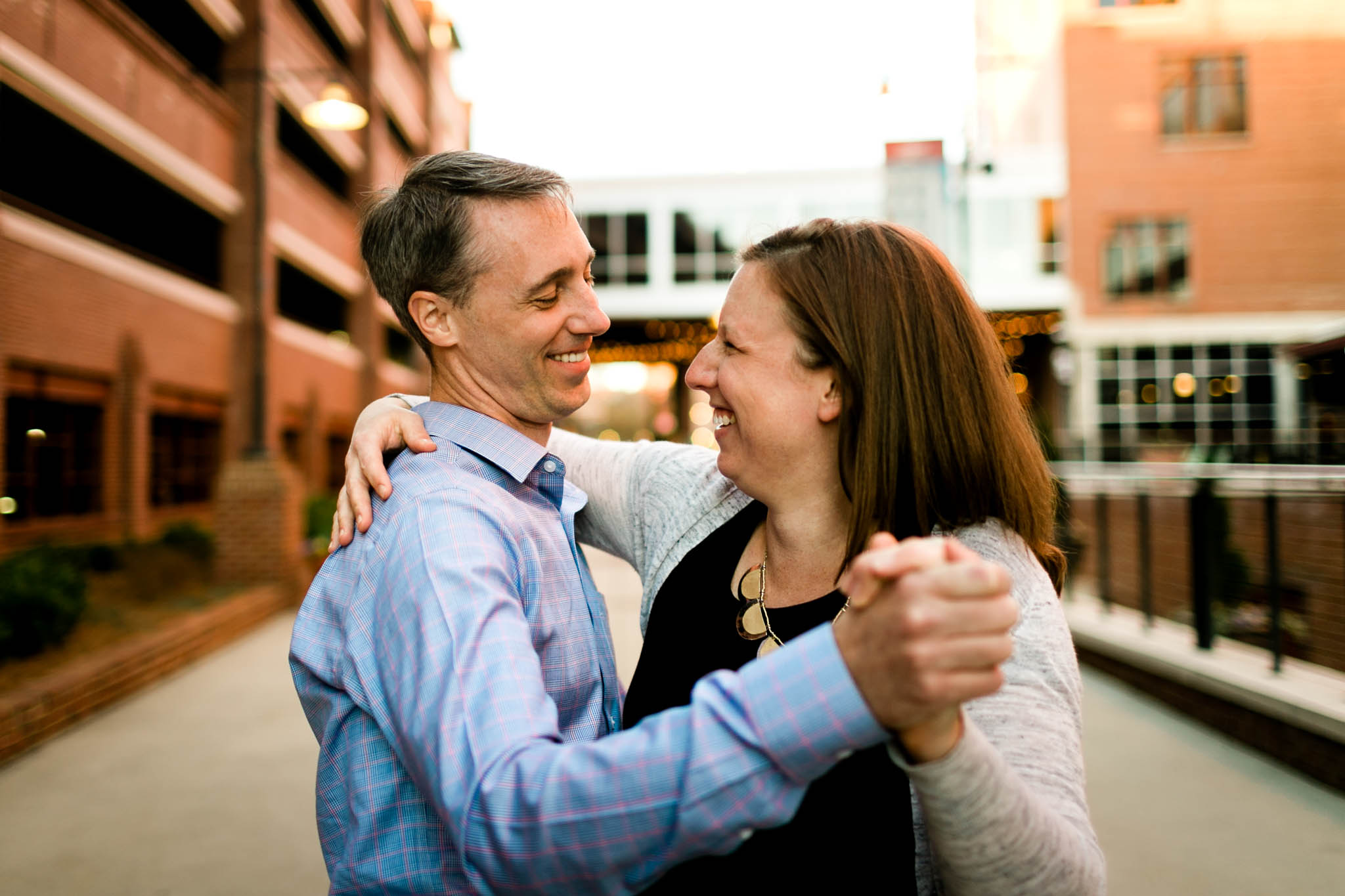Durham Photographer | Couple laughing and dancing at American Tobacco Campus | By G. Lin Photography