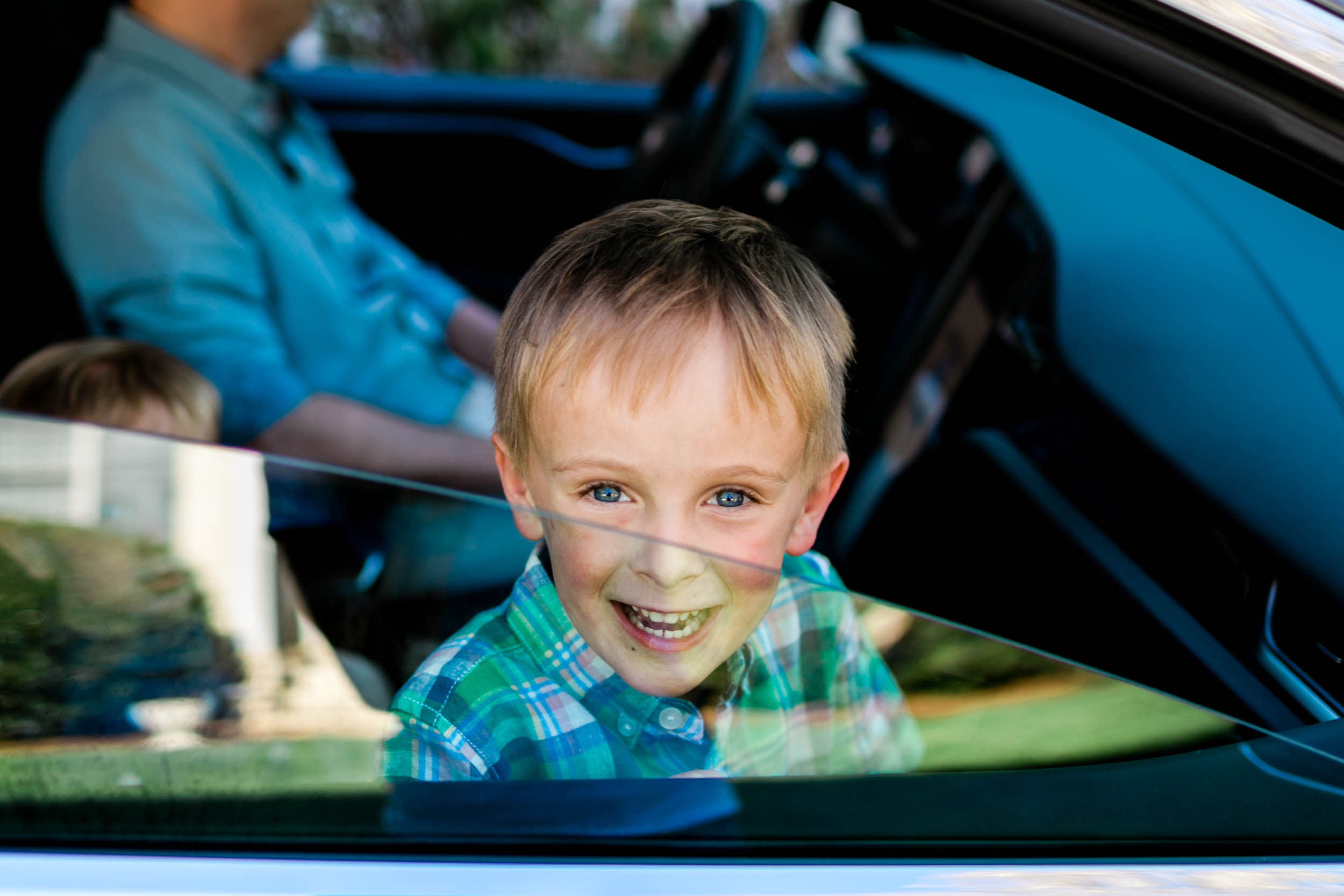 Boy sitting inside of car and smiling | Durham Family Photographer | By G. Lin Photography