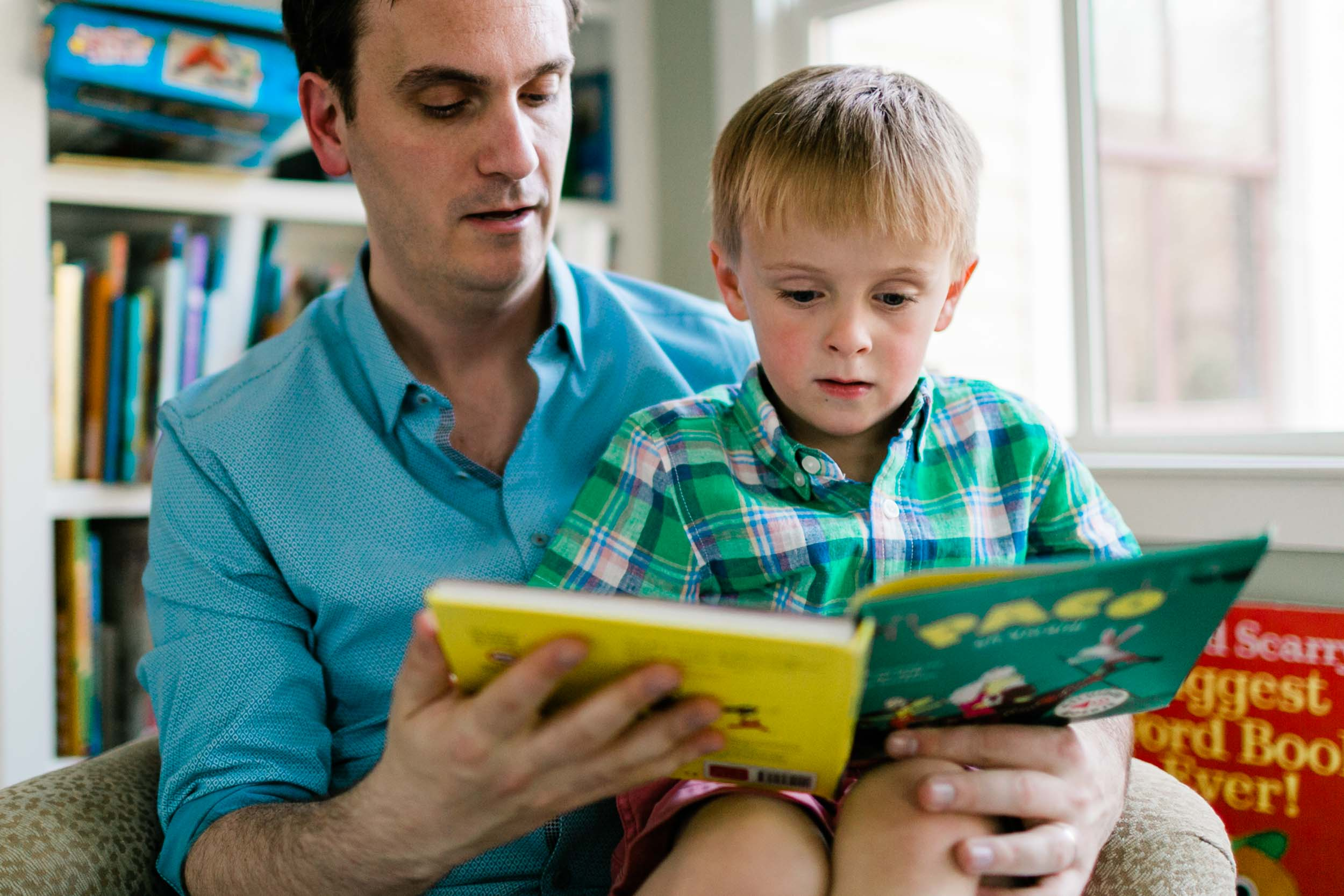 Father reading book with son on sofa | Raleigh Family Photographer | By G. Lin Photography