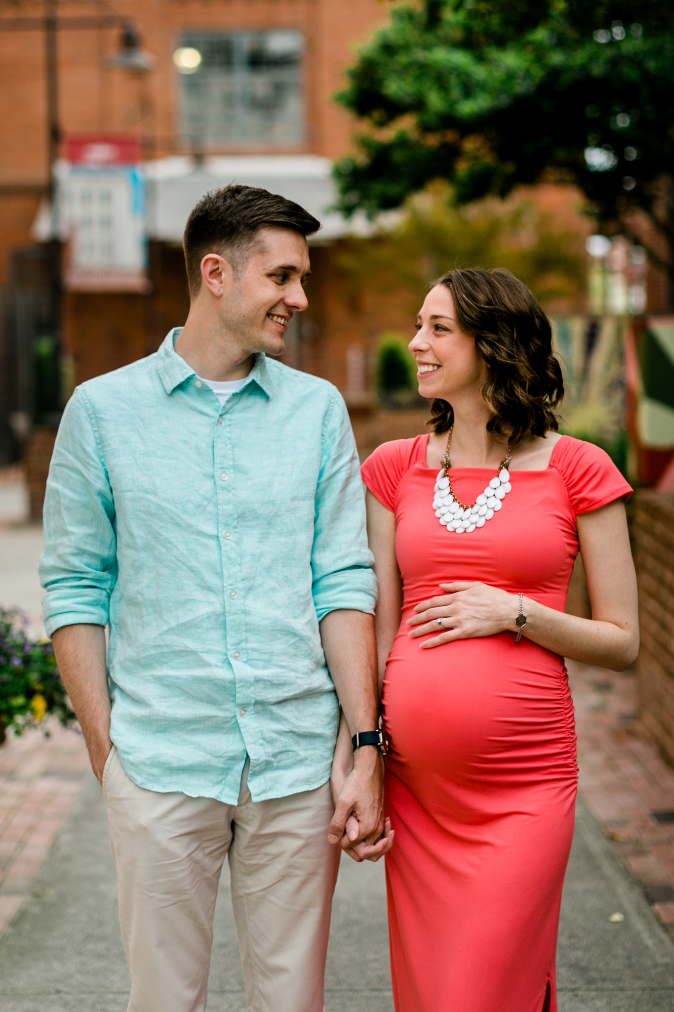 Couple smiling at each other and holding hands | Durham Newborn Photographer | By G. Lin Photography