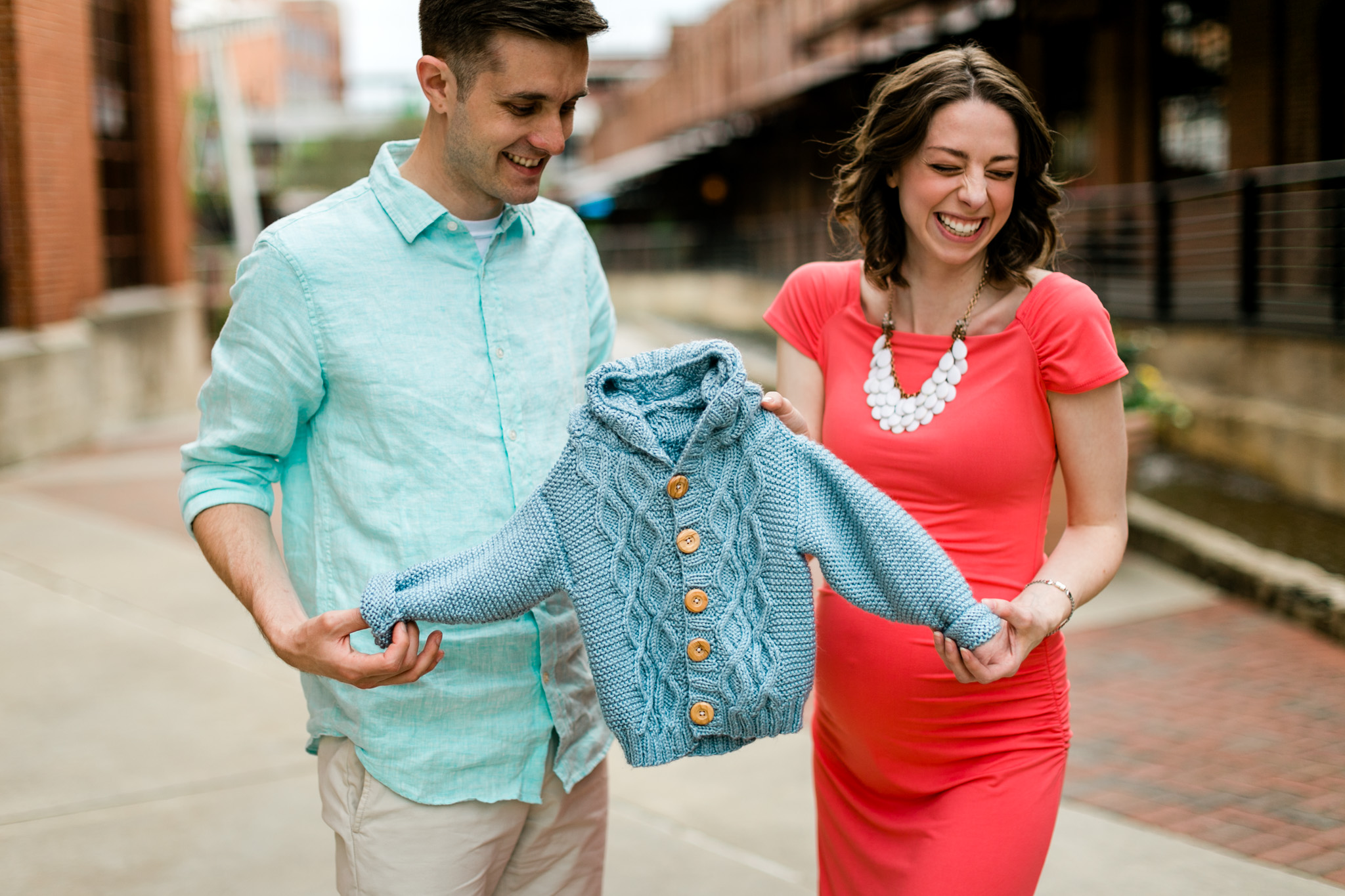 Couple holding baby sweater and laughing | Raleigh Family Photographer