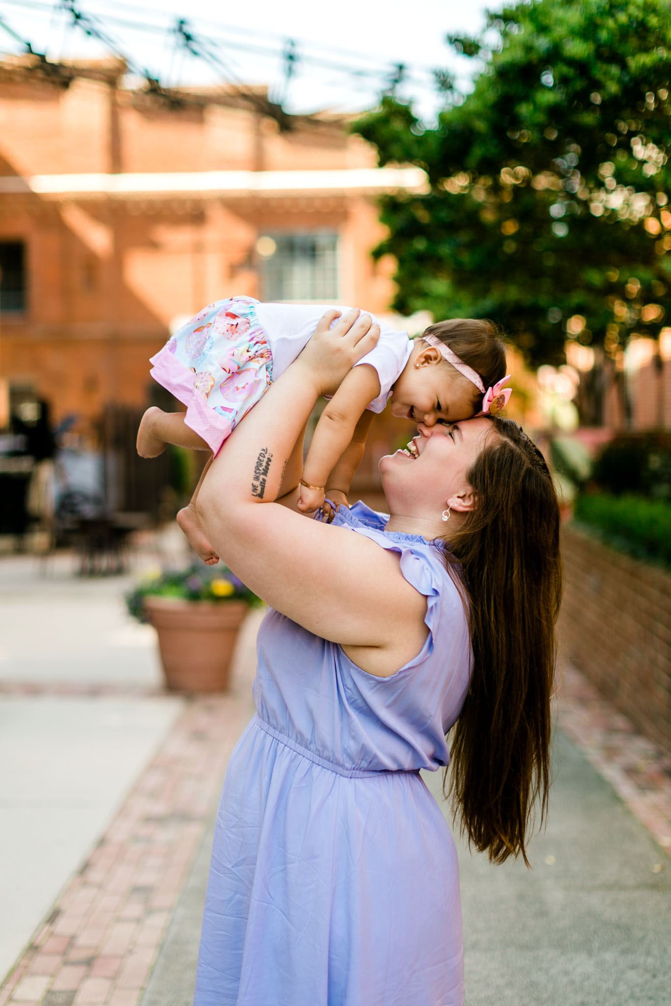Mother holding baby girl in the air at American Tobacco Campus | Durham Photographer | By G. Lin Photography