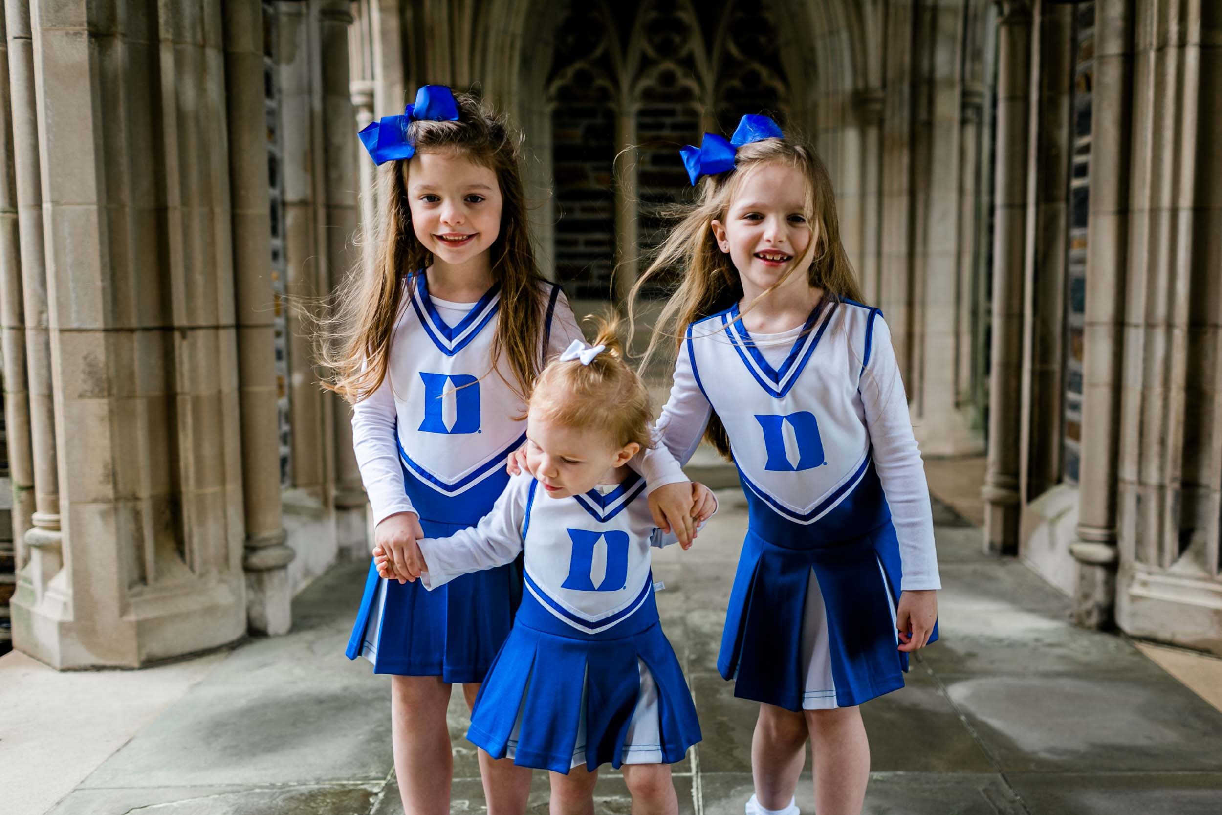Candid photo of sisters wearing Duke Cheerleader outfits | Durham Family Photographer | By G. Lin Photography
