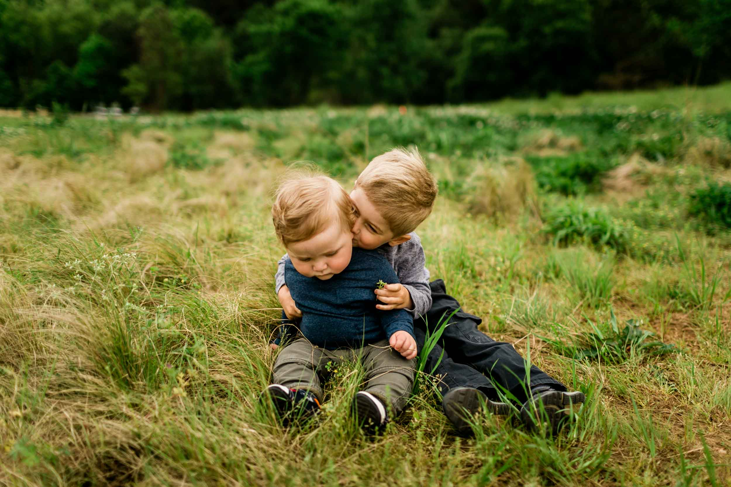 Cute photo of brothers sitting on the grass | Raleigh Family Photographer | By G. Lin Photography