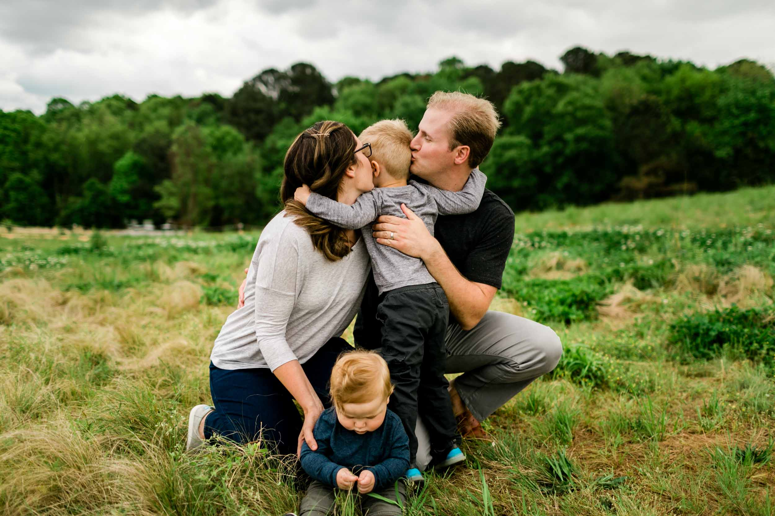Parents kissing son on cheeks | Raleigh Family Photographer | By G. Lin Photography