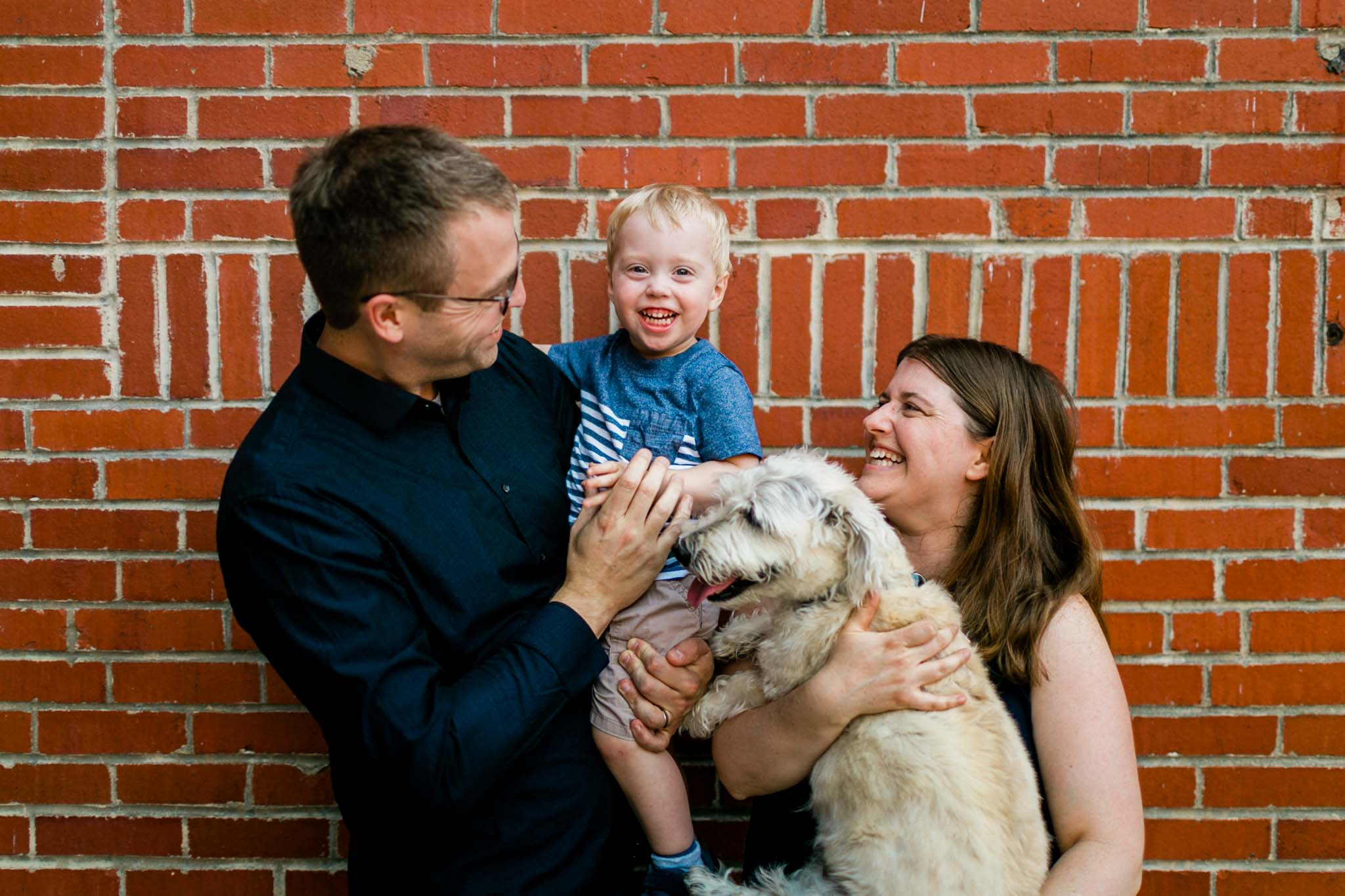 Family laughing together with brick background | Durham Photographer | By G. Lin Photography
